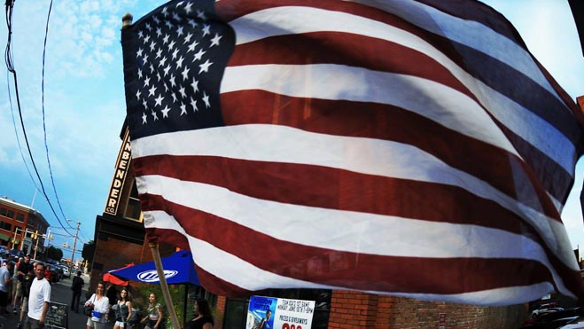 Soccer fan waves the U.S. Flag in downtown Scranton, Pa. on Monday, June 16, 2014.