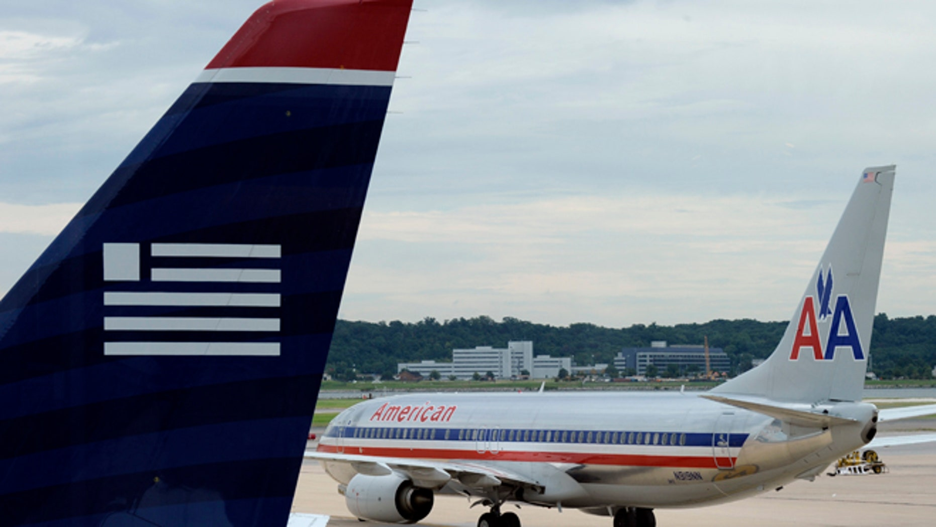 FILE: Aug. 13, 2013: An American Airlines and US Airways planes parked at Ronald Reagan National Airport in Arlington, Va.
