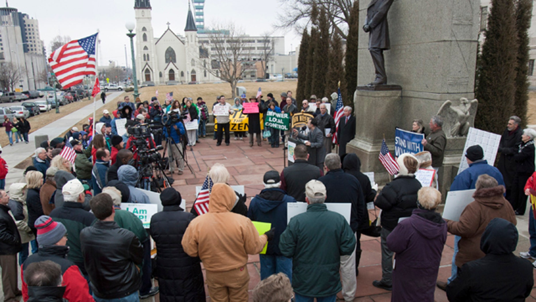 Participants in a rally  sponsored by Americans for Prosperity gather under a statue of Abraham Lincoln, outside the Nebraska State Capitol in Lincoln, Neb., Friday, March 4, 2011