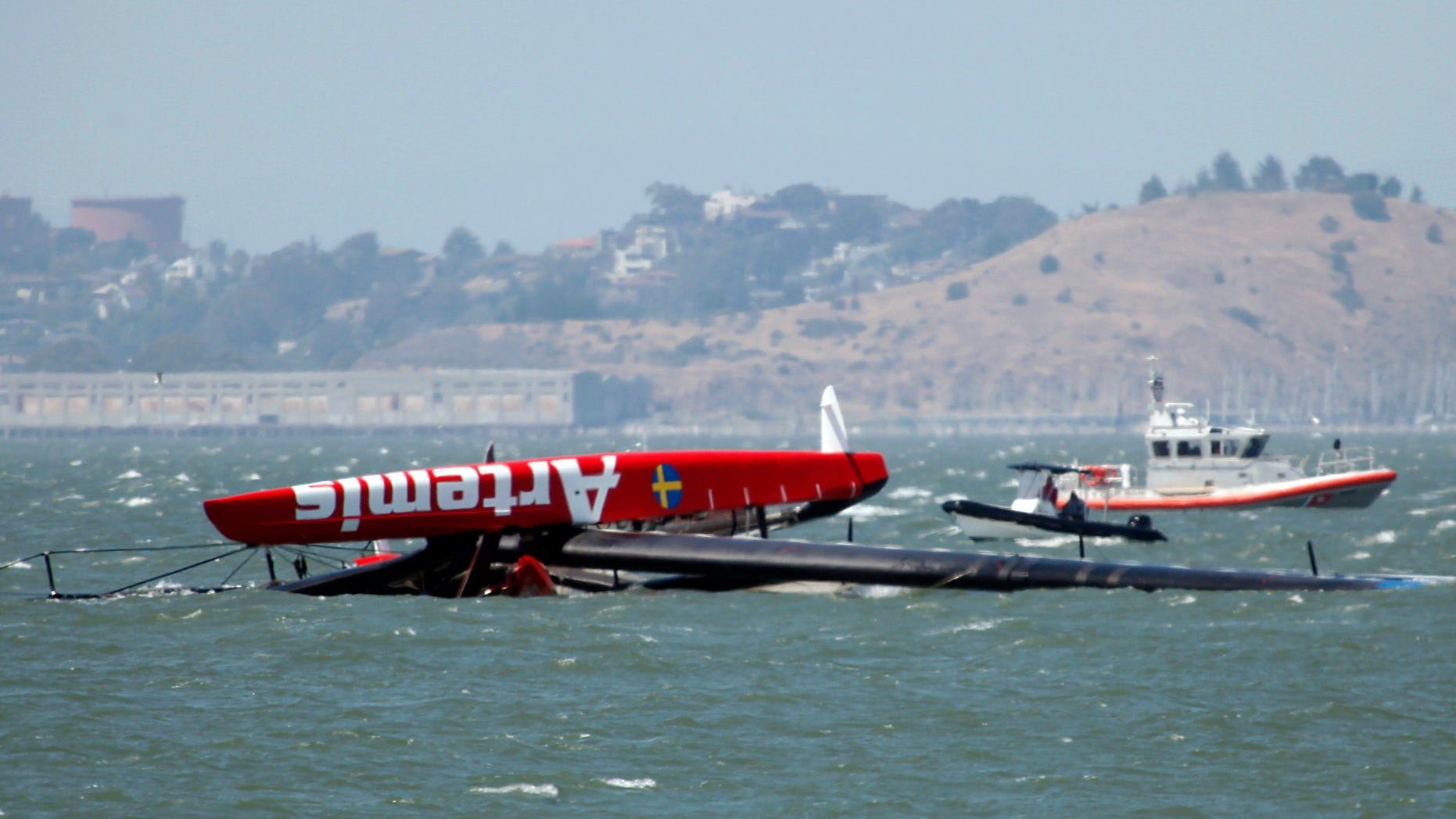 May 9, 2013: The overturned Artemis Racing AC72 catamaran, an America's Cup entry from Sweden, is towed past Treasure Island after the boat capsized during training in San Francisco Bay in San Francisco, Calif.