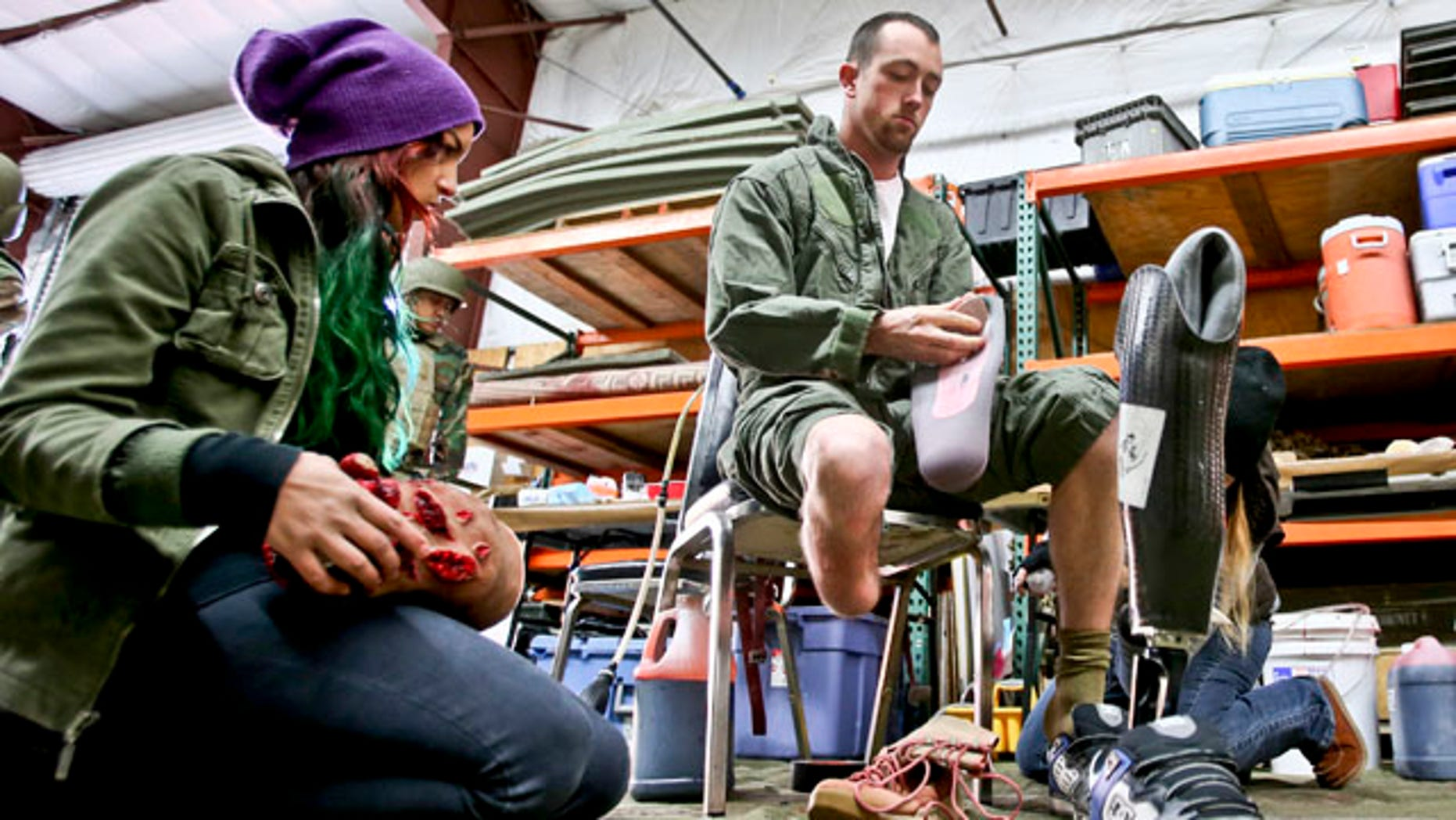 Feb. 12, 2013: Former Navy corpsman Joel Booth, who lost a leg in Afghanistan, prepares with the help of a makeup artist to play his role as a downed helicopter pilot in a military training exercise at San Diego-based Strategic Operation.