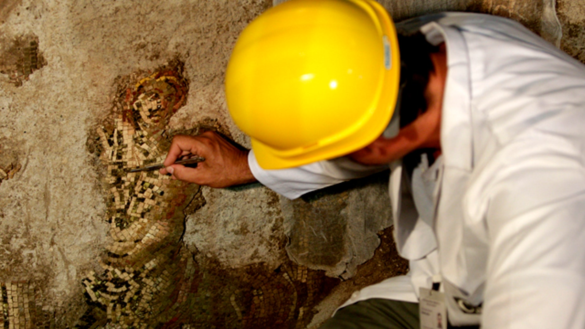 July 29, 2011: An archaeologist works on a portrait of a Centaur, part of a mosaic discovered in downtown Rome following excavations in the bowels of an ancient hill.