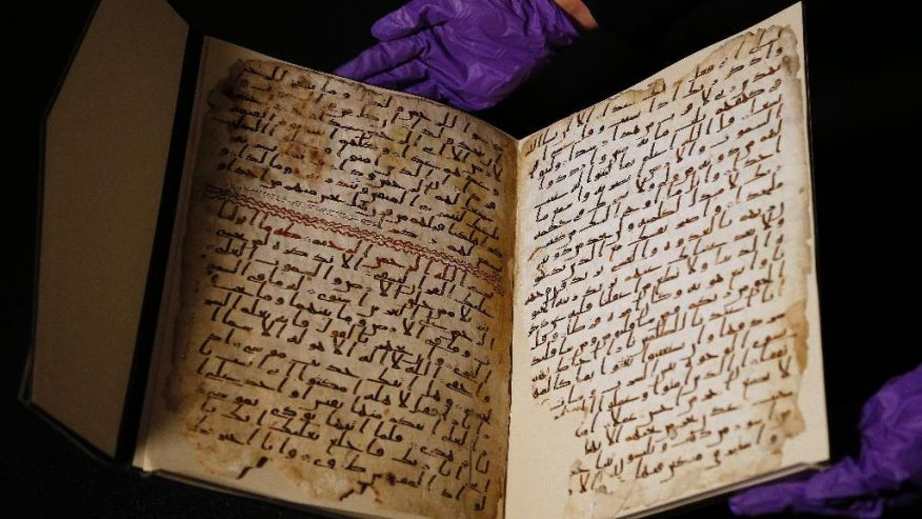 July 22, 2015: A university assistant shows fragments of an old Koran at the University in Birmingham, U.K.