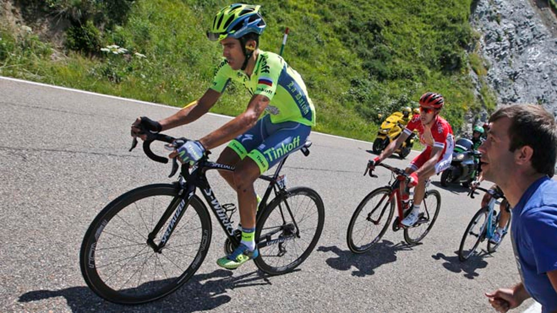 Spain's Alberto Contador, left, strains as he rides in the back of the pack with Franceâs Nicolas Edet, right, during the ninth stage of the Tour de France cycling race over 184.5 kilometers (114.3 miles) with start in Vielha Val d'Aran, Spain, and finish in Andorra Arcalis, Andorra, Sunday, July 10, 2016. (AP Photo/Christophe Ena)
