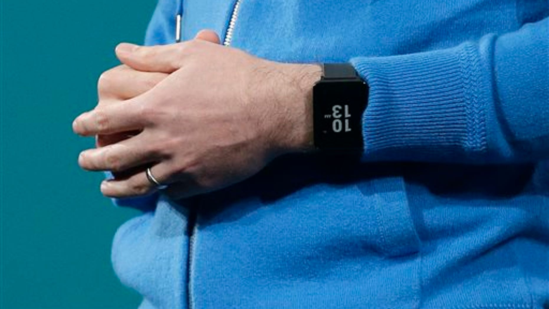David Singleton, Android director of engineering, wears an Android Wear watch on his wrist while speaking at the Google I/O 2014 keynote presentation in San Francisco, Wednesday, June 25, 2014. As the Internet giant's Android operating system stretches into cars, homes and smartwatches, this year's annual confab will expand on its usual focus on smartphones and tablets. (AP Photo/Jeff Chiu)