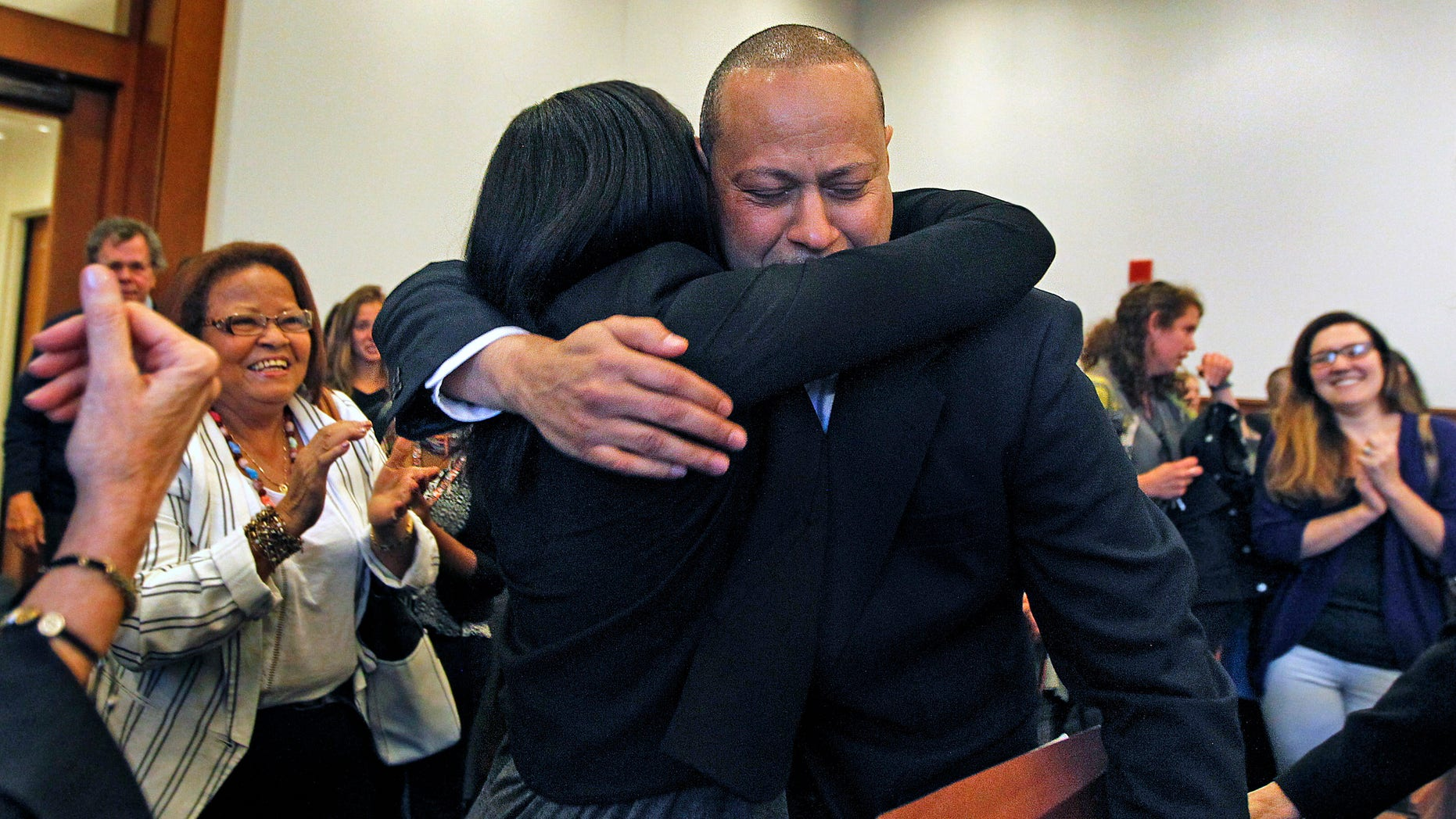 Angel Echavarria hugs his daughter after he is released in Salem Superior Court on May 18, 2015.