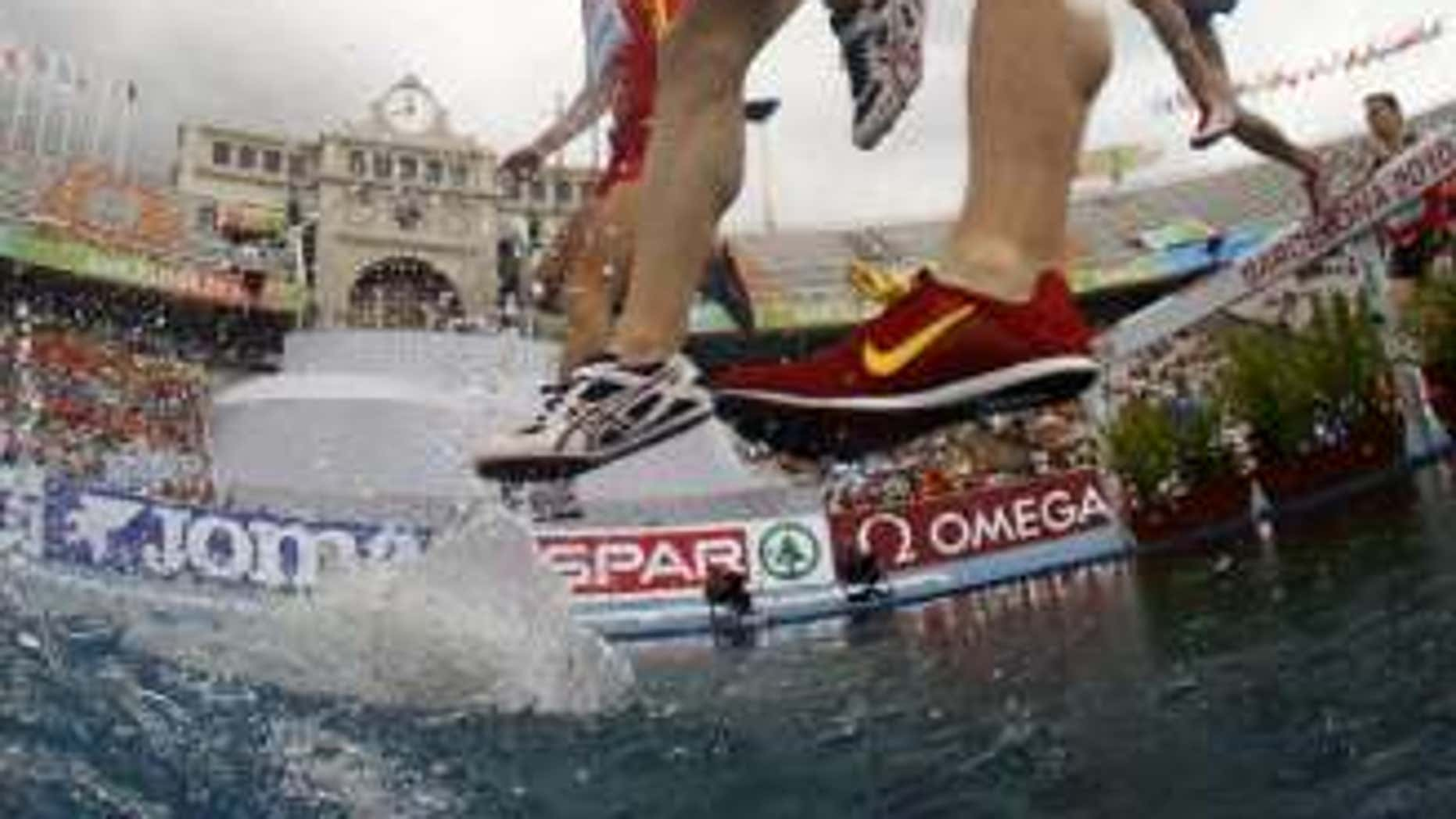 July 30, 2010: Angel Mullera of Spain and Hubert Pokrop of Poland jump a water obstacle in the men's 3000 metres steeplechase heats at the European Athletics Championships in Barcelona.