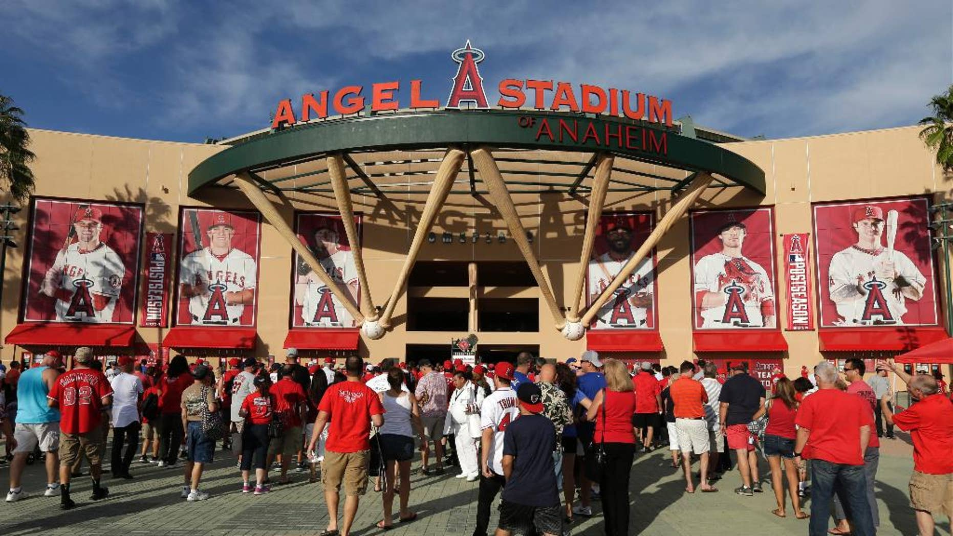 FILE - In this Oct. 3, 2014, file photo, fans enter Angel Stadium of Anaheim before Game 2 of baseball's AL Division Series between the Los Angeles Angels and the Kansas City Royals in Anaheim, Calif. In Southern California, police are looking Monday, Oct,. 6 for three men suspected of brutally beating a man in the Angels Stadium parking lot after the Angels' playoff night game on Friday, Oct. 3. (AP Photo/Gregory Bull, File)