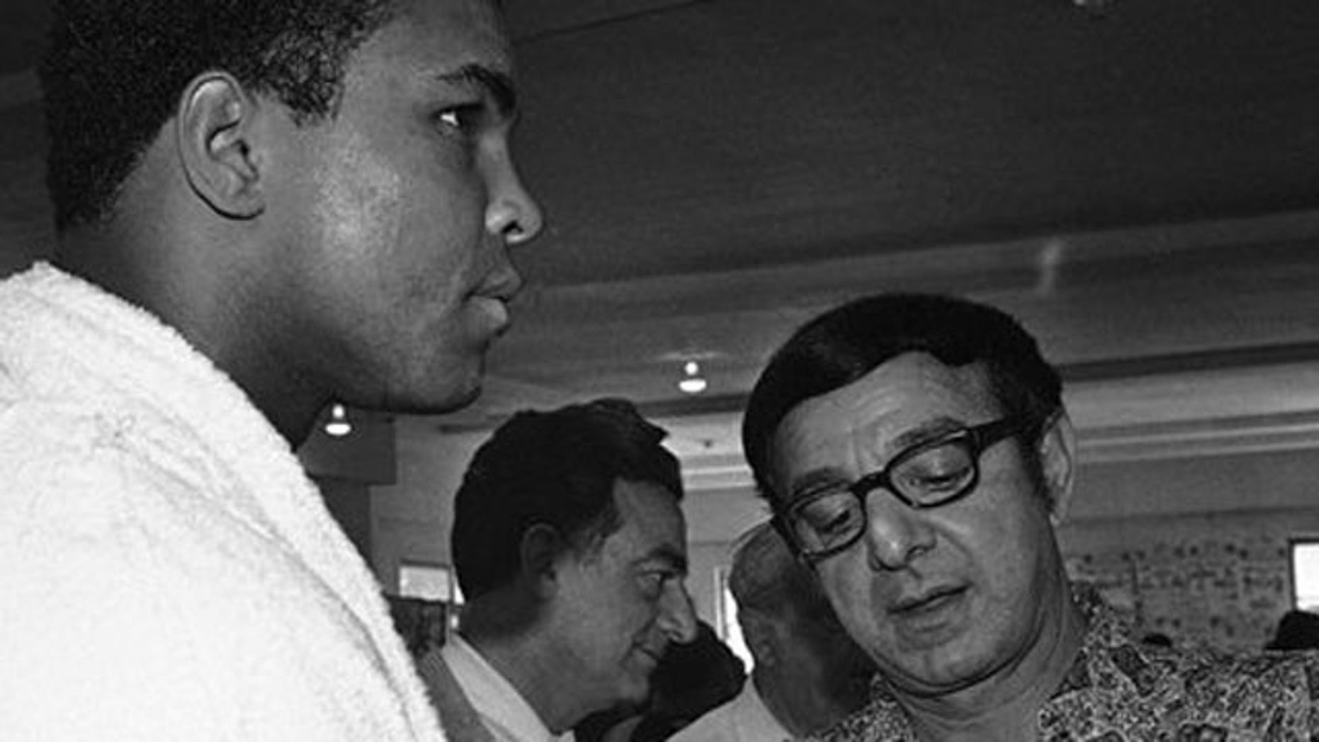 FILE - In this March 4, 1971, file photo, heavyweight challenger Muhammad Ali, left, has fists taped by trainer Angelo Dundee in Miami Beach as Ali resumes his training for an upcoming title bout with champion Joe Frazier in Madison Square Garden.