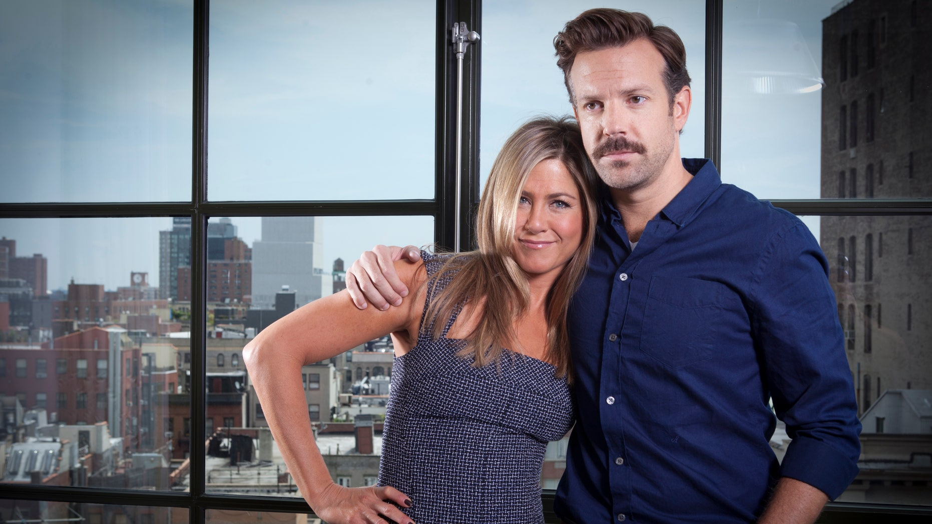 """FILE - In this July 27, 2013 file photo, actor Jason Sudeikis, right, and actress Jennifer Aniston pose for a portrait as they promote the movie """"We're the Millers"""" in New York. The film opens nationwide on Wednesday, Aug. 7. (Photo by Carlo Allegri/Invision/AP, File)"""