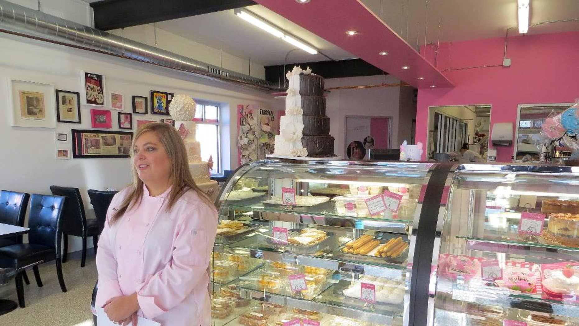 In this Jan. 20, 2015 photo, bakery owner Marjorie Silva stands for a photo inside her own Azucar Bakery, in Denver. Silva is facing a discrimination complaint with Colorado's Civil Rights Division because she refused to write hateful words about gays on a cake for a customer. (AP Photo/Ivan Moreno)