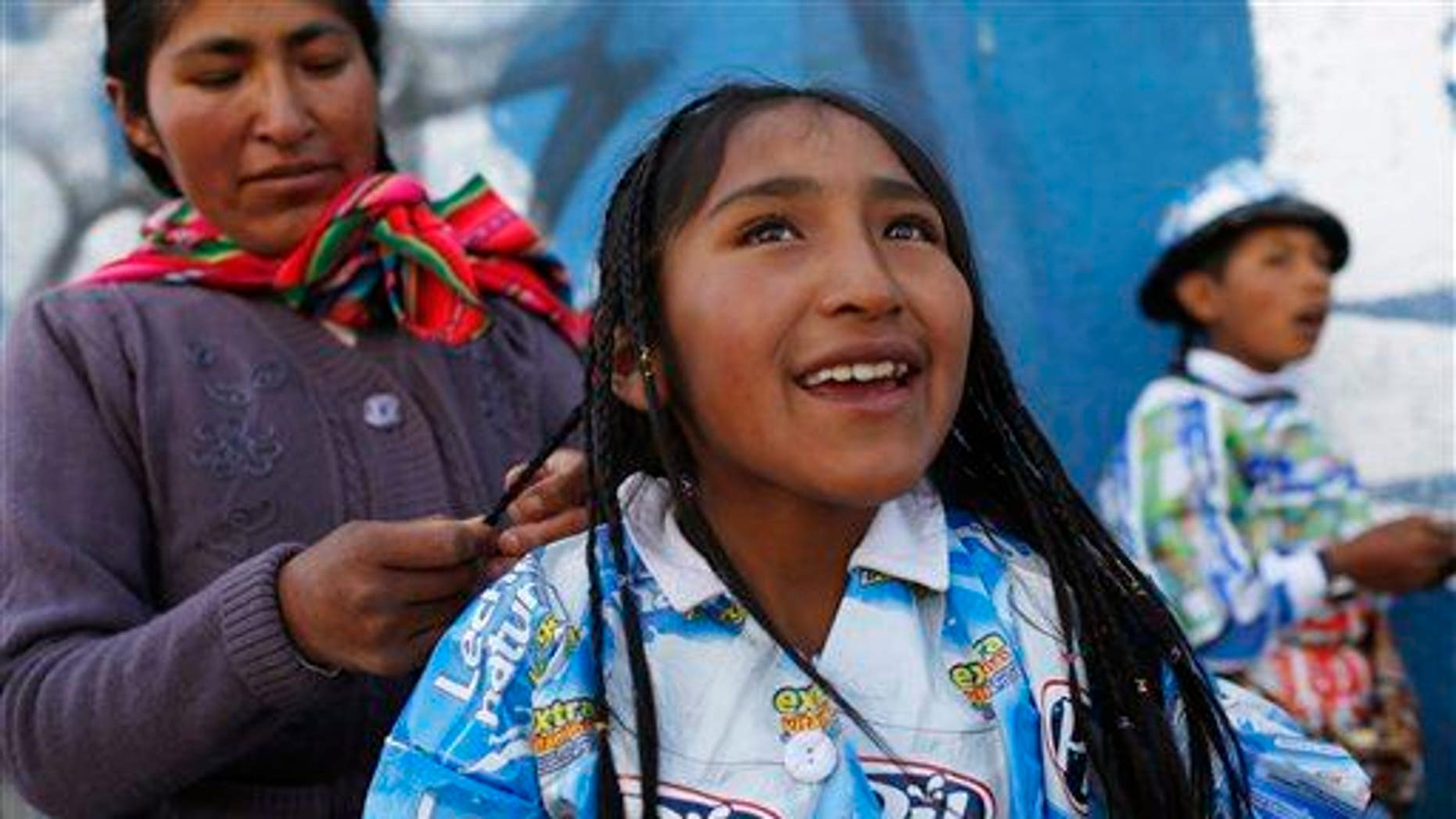 An indigenous woman braids her daughter's hair before the start of a parade in El Alto, Bolivia, Friday, Oct. 23, 2015.