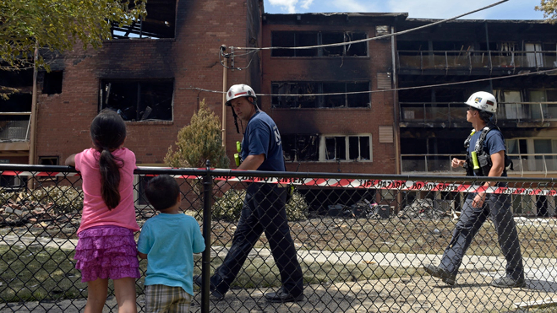 People view the scene of an apartment building fire in Silver Spring, Md., Thursday, Aug. 11, 2016.