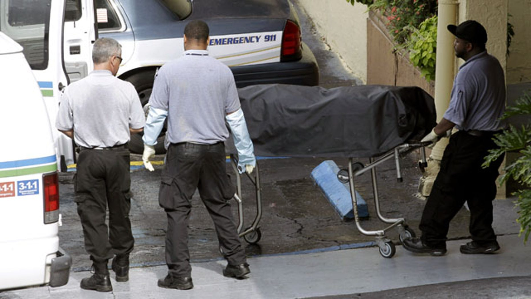 July 27, 2013: Miami-Dade morgue workers carry out a body out at the scene of a fatal shooting in Hialeah, Fla. (AP Photo)