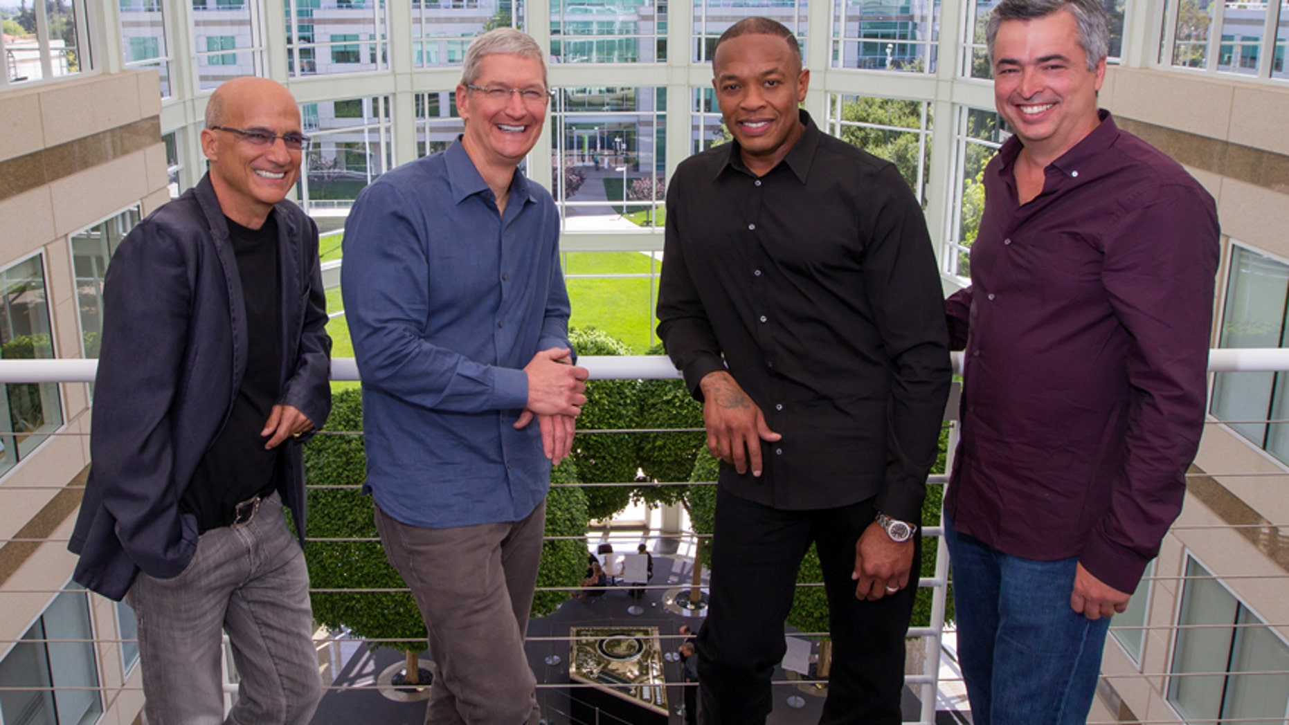 In this image provided by Apple, from left to right, music entrepreneur and Beats co-founder Jimmy Iovine, Apple CEO Tim Cook, Beats co-founder Dr. Dre, and Apple senior vice president Eddy Cue pose together at Apple headquarters in Cupertino, Calif., Wednesday, May 28, 2014. Apple is striking a new chord with a $3 billion acquisition of Beats Electronics, a headphone and music streaming specialist that also brings the swagger of rapper Dr. Dre and recording impresario Jimmy Iovine.