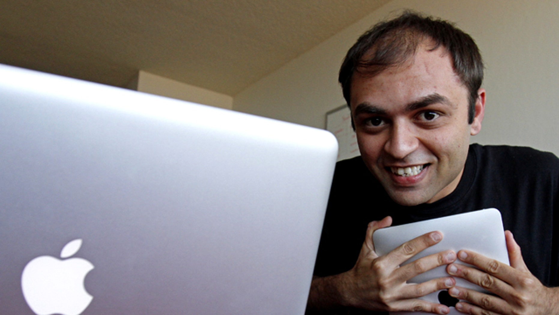 """Cupidtino founder Mel Sampat hugs his Apple iPad in San Francisco. The site aims to connect Apple aficionados with like-minded """"Machearts."""" The idea is that if you love the iPhone you might be best suited to date a fellow Apple fan."""