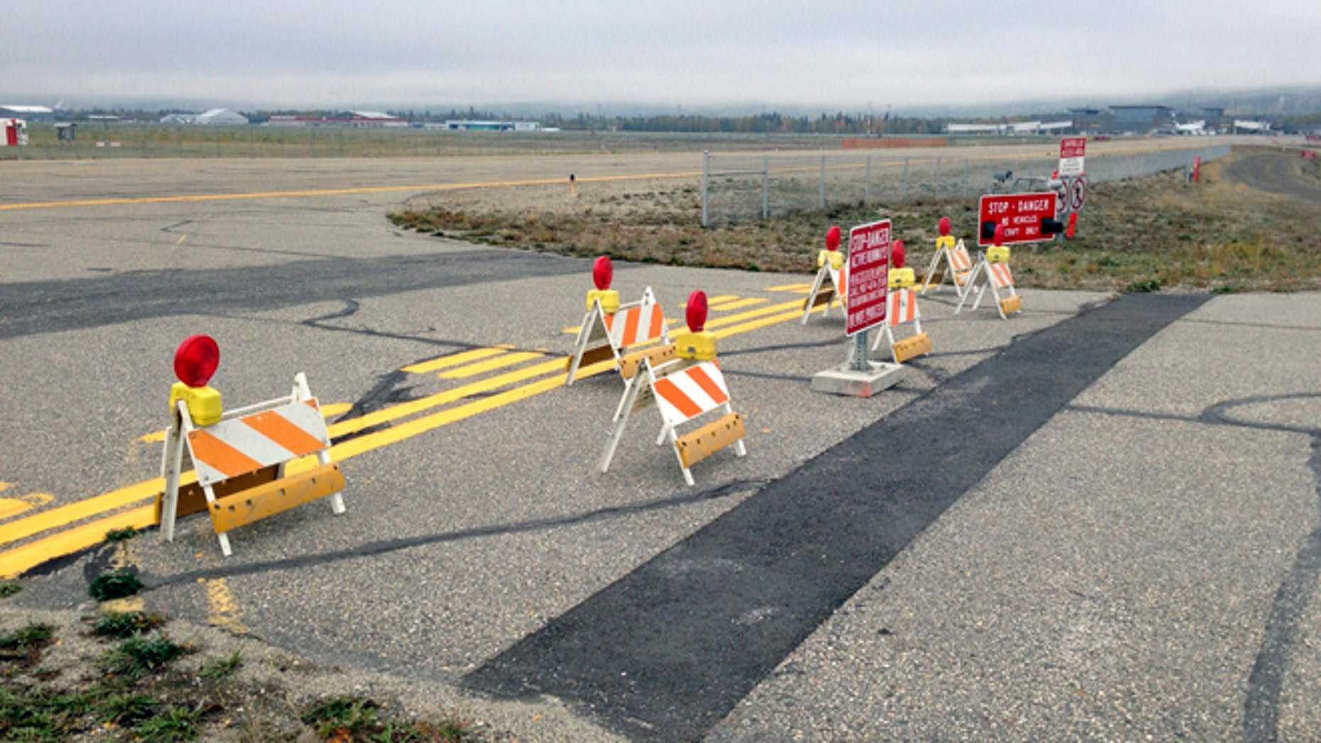 This Sept. 20, 2013 image provided by the Fairbanks International Airport shows the barricaded entrance to a taxiway, at Float Pond Road blocking access to Taxiway B in Fairbanks,  Alaska. A glitch in the Apple Maps app on newer iPhones and iPads guides people up to this runway at Fairbanks International Airport instead of the proper route to the terminal. (AP Photo/Fairbanks International Airport)