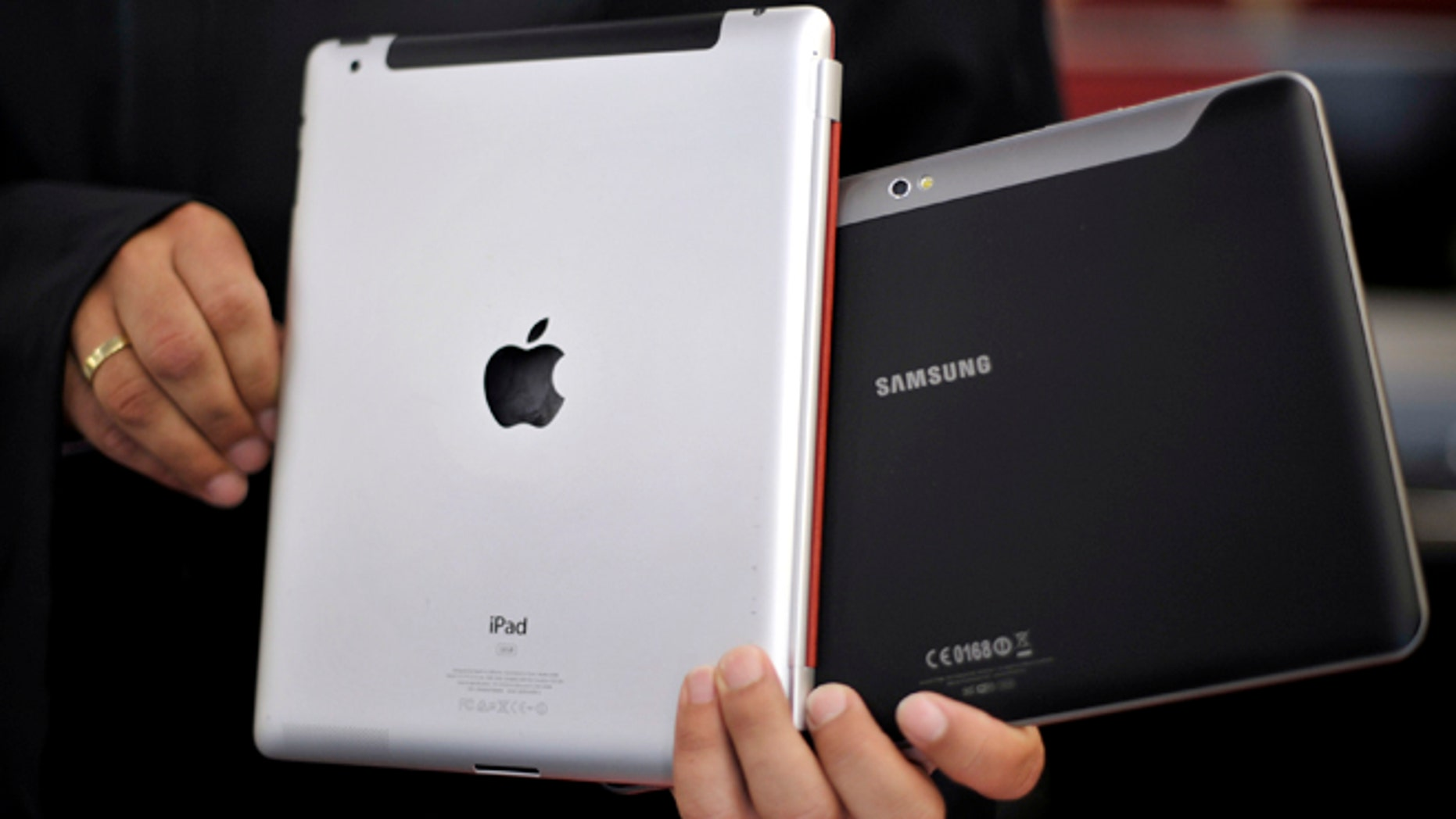Aug. 25, 2011: An attorney holds an Apple iPad, left, and a Samsung Galaxy Tab 10.1 at the regional court in Duesseldorf, Germany.