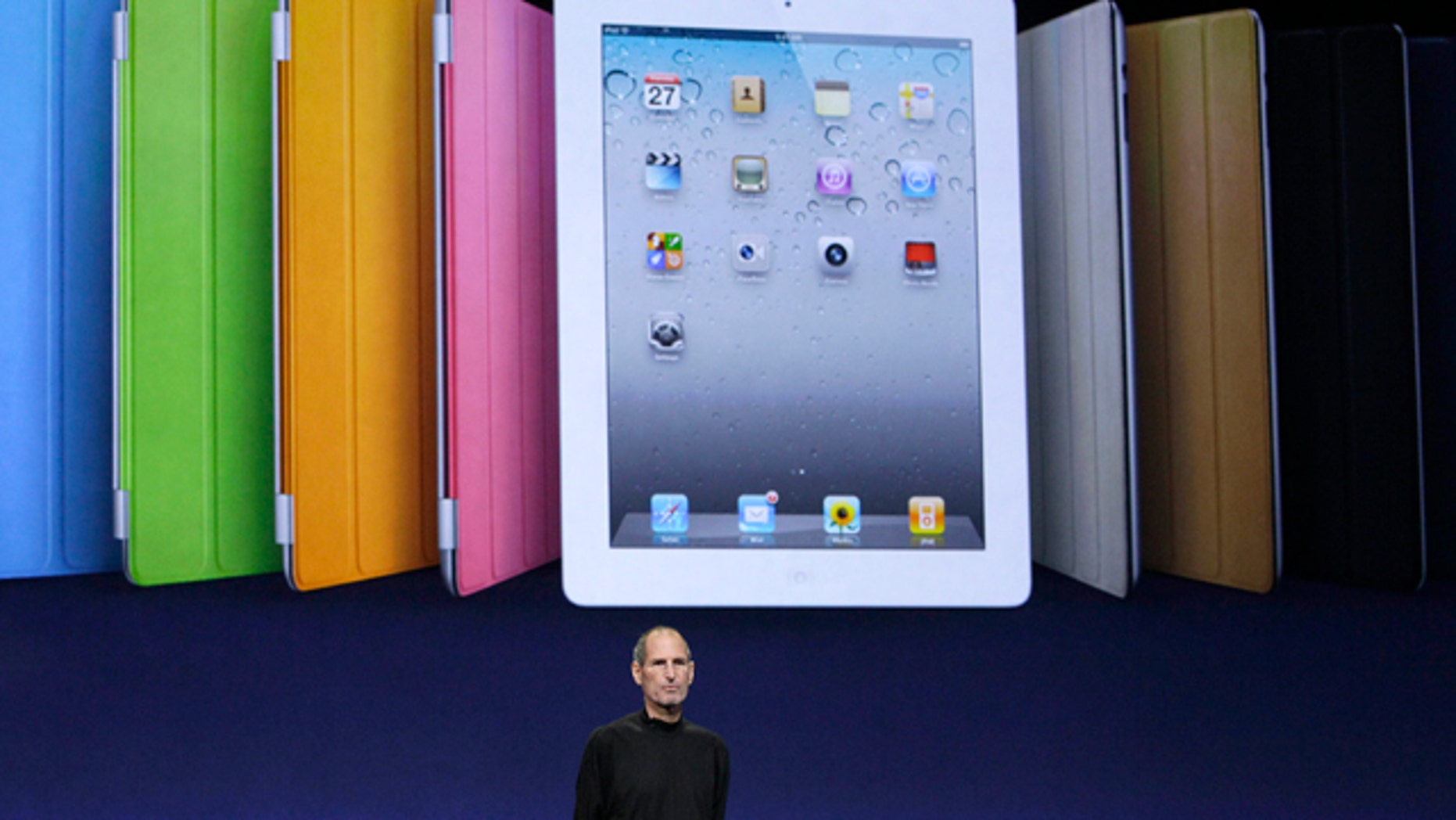Apple chairman and CEO Steve Jobs stands under an image of the iPad 2 at an Apple event at the Yerba Buena Center for the Arts Theater in San Francisco, Wednesday, March 2, 2011.