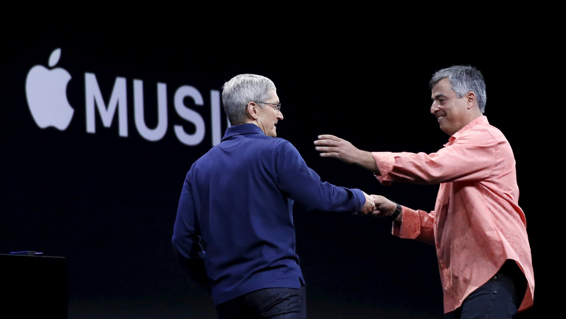File photo: Apple CEO Tim Cook (L) greets senior vice president of internet services and software Eddy Cue during his keynote address at the Worldwide Developers Conference in San Francisco, California June 8, 2015.