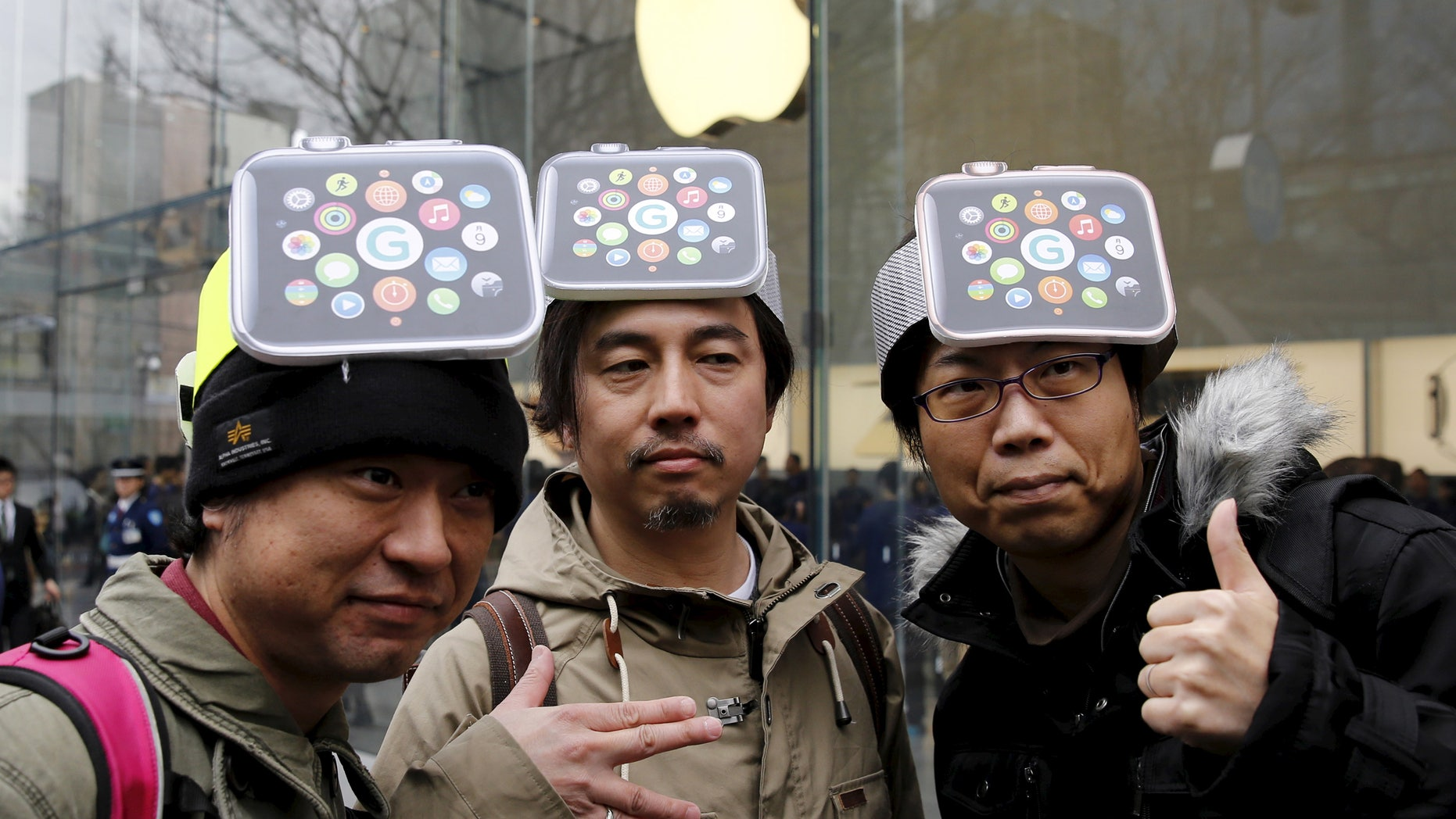 Men wearing cardboard hats depicting the Apple Watch, pose for photos before it goes on display in front of the Apple Store in Tokyo's Omotesando shopping district April 10, 2015.