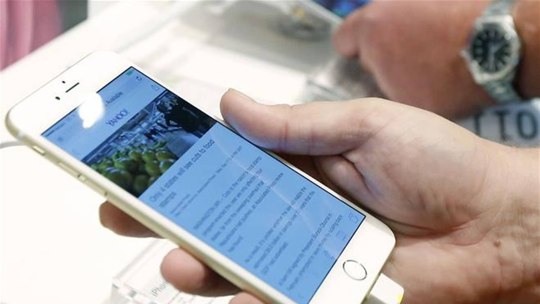 In this Sept. 19, 2014, file photo, a customer looks at the screen size on an iPhone 6 Plus.