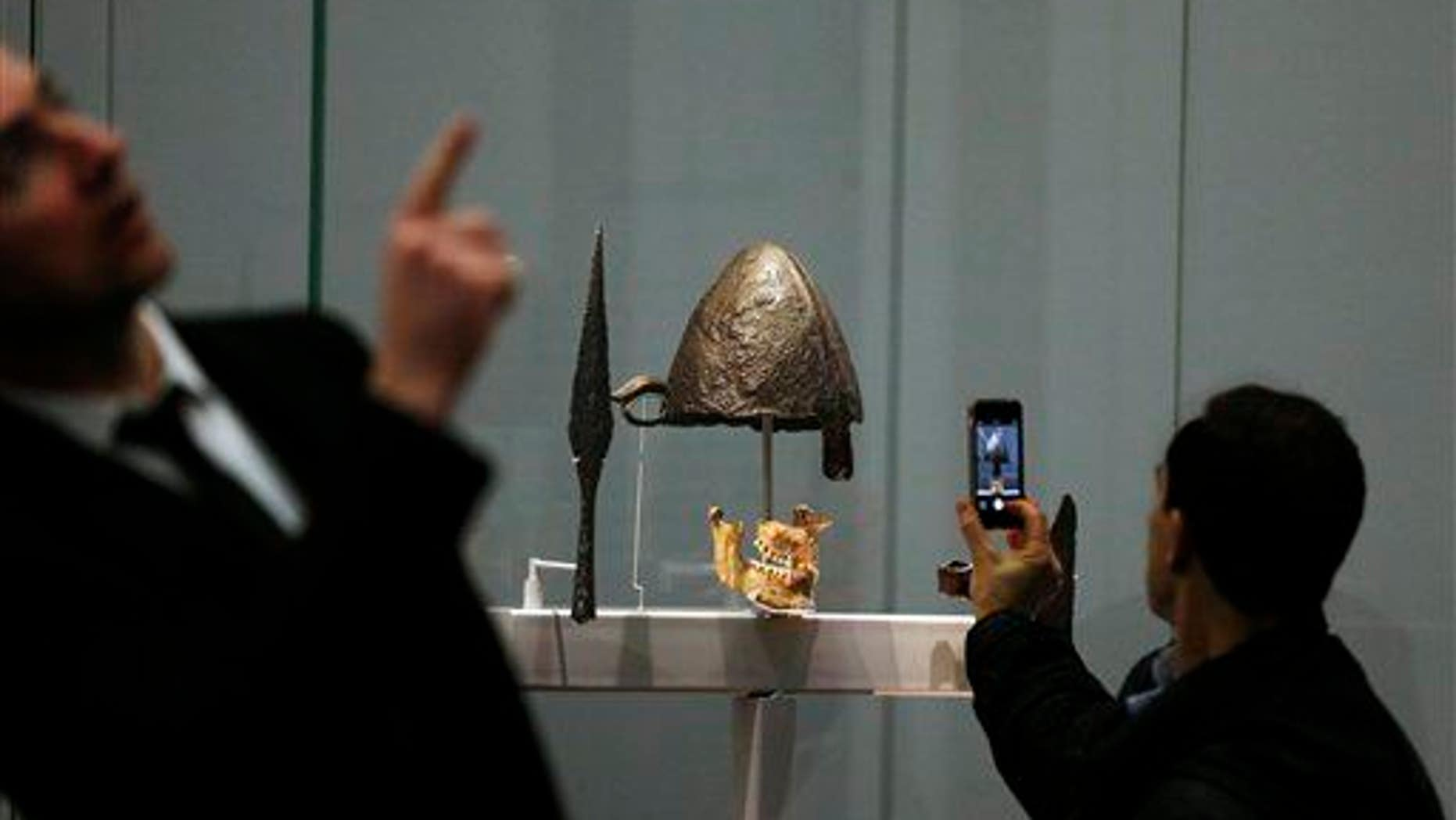 A visitor takes pictures at a display of helmets and weapons at an exhibition entitled 'Vikings: Life and Legend' at the British Museum in central London, Tuesday, March 4, 2014.