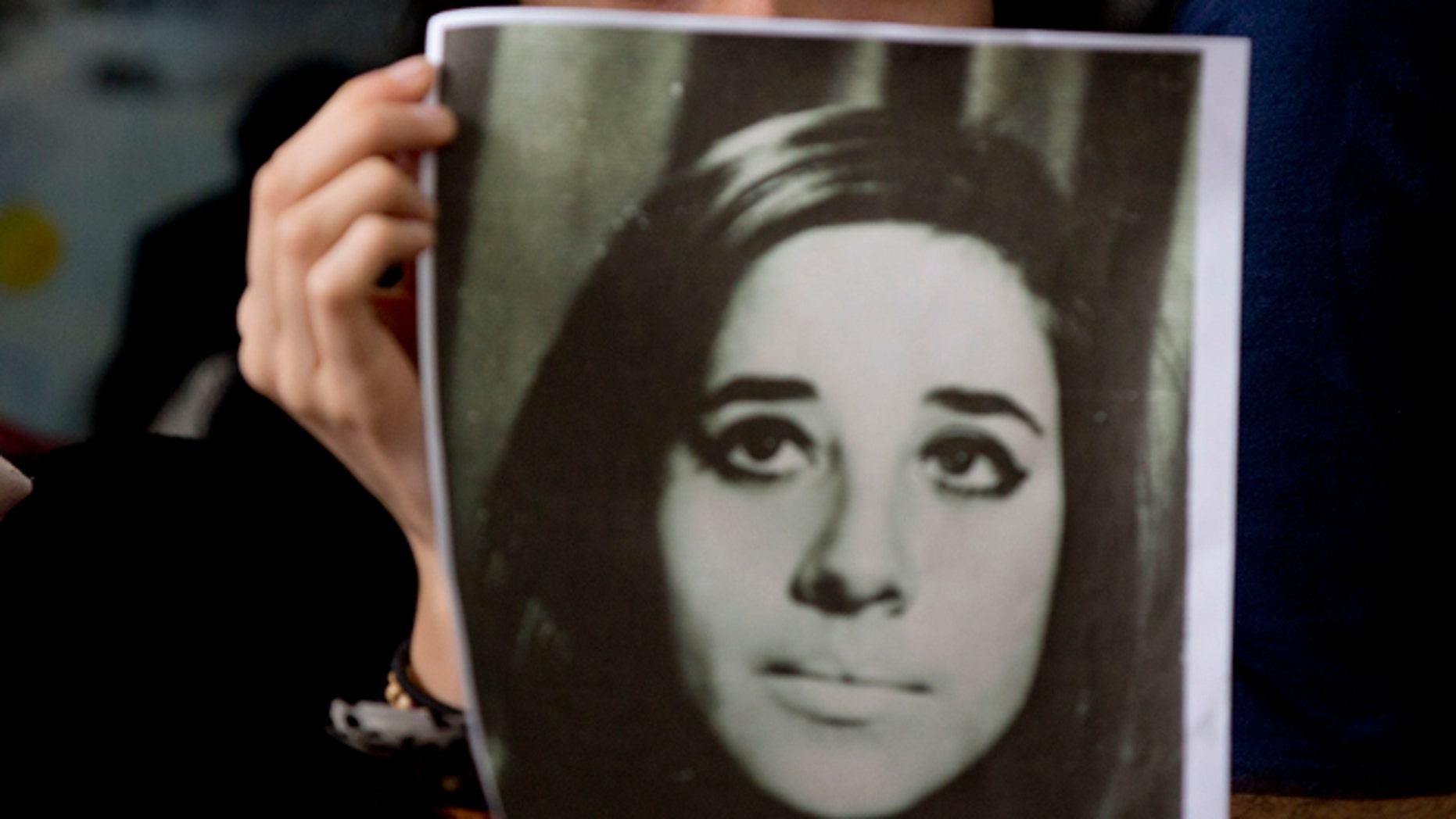 A woman holds an image of disappeared Ana Maria Lanzillotto during a press conference in Buenos Aires on Oct. 5, 2016.