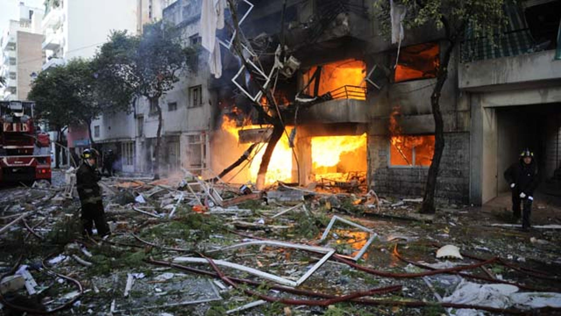 August 6, 2013: Firemen stand in debris caused by a gas explosion that has severely damaged a multi-story apartment building in Rosario, Argentina. The explosion ripped off the building's facade and also damaged other buildings for blocks around. (AP Photo)