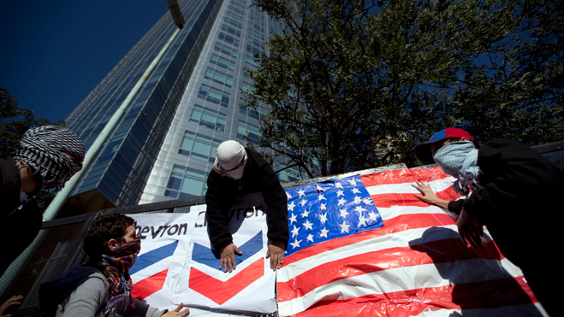 Demonstrators place a U.S. flag and a Chevron sign on a fence in front of Argentina's state-controlled YPF oil company headquarters to protest a deal between YPF and U.S. oil company Chevron in Buenos Aires, Argentina, Tuesday, July 16, 2013. YPF, which was expropriated in 2012 from Spain's Repsol, is finalizing the details of an agreement with Chevron which would invest in the first pilot for massive exploration for unconventional oil and gas in the Vaca Muerta region. (AP Photo/Victor R. Caivano)