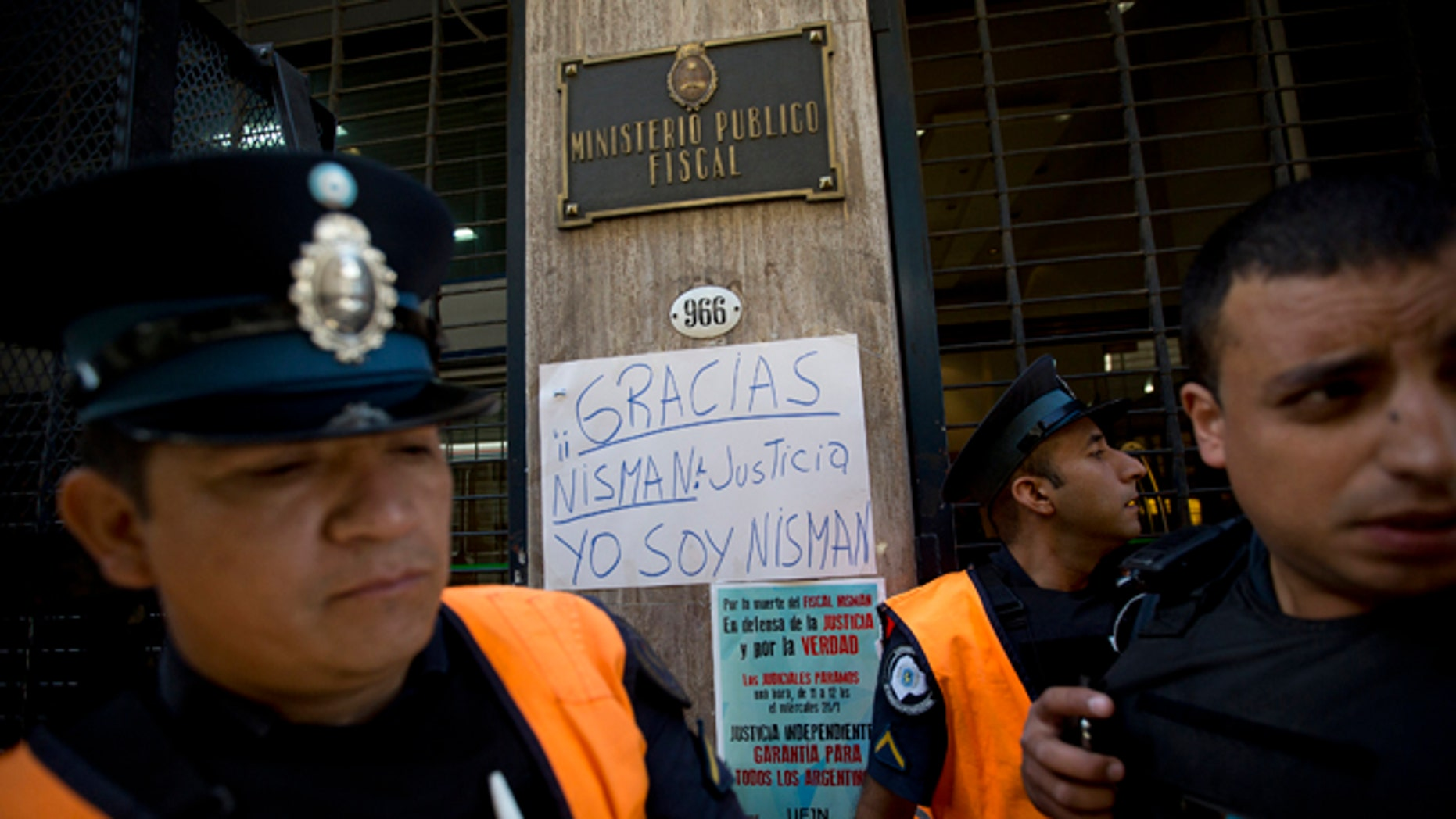 "Policemen stand guard next to a sign that reads in Spanish; ""Thanks Nisman. Justice. I am Nisman,"" outside the prosecutor's office investigating the death of Alberto Nisman, a prosecutor found dead in his apartment, in Buenos Aires, Argentina, Thursday, Jan. 22, 2015. The death of the prosecutor who had accused Argentinas President Cristina Fernandez of a criminal conspiracy came under mounting questions Wednesday with the discovery that the apartment where he was found dead had not been securely locked and had a third entrance. (AP Photo/Rodrigo Abd)"