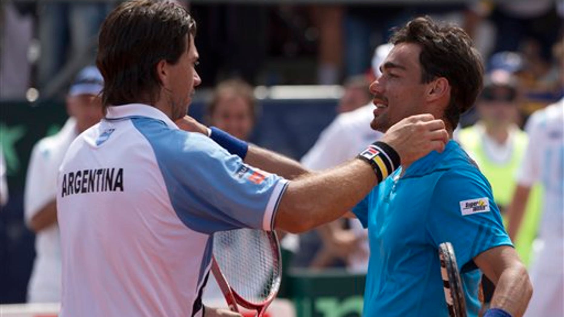 Argentina's Carlos Berlocq, left, and  Italy's Fabio Fognini embrace at the end of their Davis Cup singles match, in Mar del Plata, Argentina, Sunday, Feb. 2, 2014. Fognini defeated Berlocq 7-6, 4-6, 6-1, 6-4 to give Italy a 3-1 victory. (AP Photo/Eduardo Di Baia)