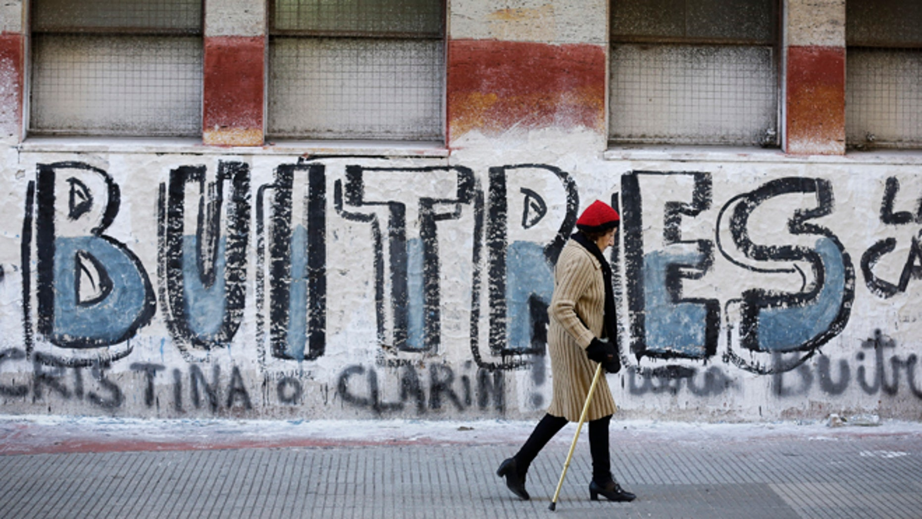 """A woman walks by a graffiti that reads in Spanish """"Vultures"""" in Buenos Aires, Argentina."""