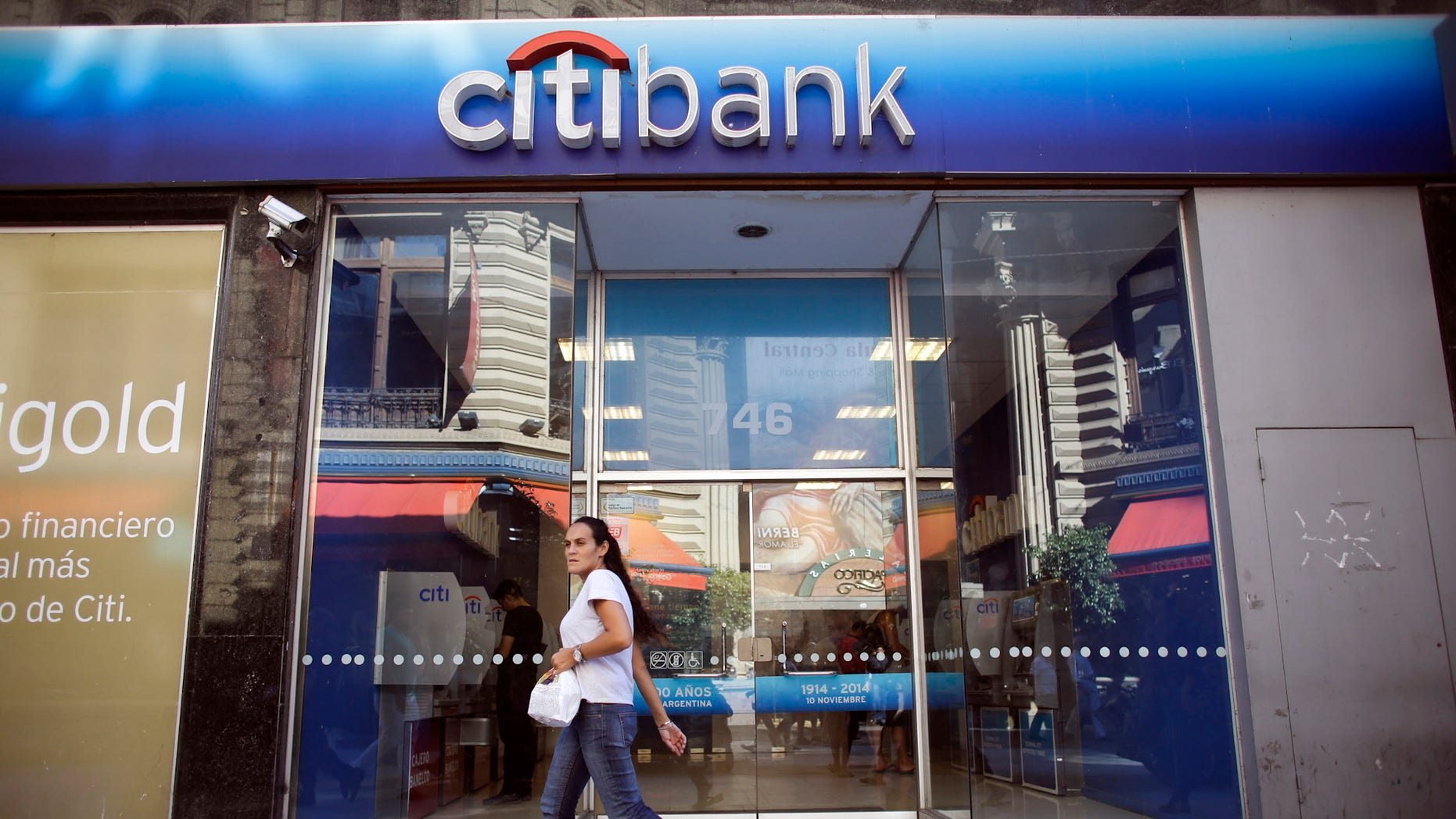 A woman walks by a Citibank branch in Buenos Aires, Argentina, Tuesday, March 17, 2015. Citibank said Tuesday it was getting out of the business of making bond payments for Argentina, the latest fallout from a bitter court fight between the South American country and a group of bondholders in the U.S. (AP Photo/Victor R. Caivano)