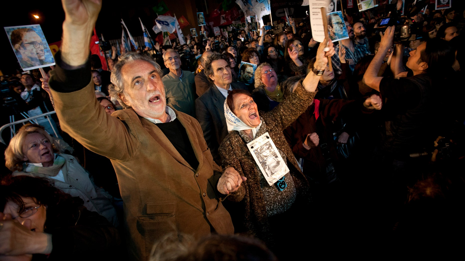 Human right activists, among them Mothers of Plaza de Mayo member Tati Almeida, second from left, celebrate after a trial against former military and police officials in Buenos Aires, Argentina, Wednesday, Oct. 26, 2011. A court in Argentina has sentenced 12 former military and police officials to life in prison for crimes against humanity committed during the country's 1976-1983 dictatorship. The men were convicted of kidnapping, torturing and killing leftist dissidents at a torture center called the Navy Mechanics School. (AP Photo/Victor R. Caivano)