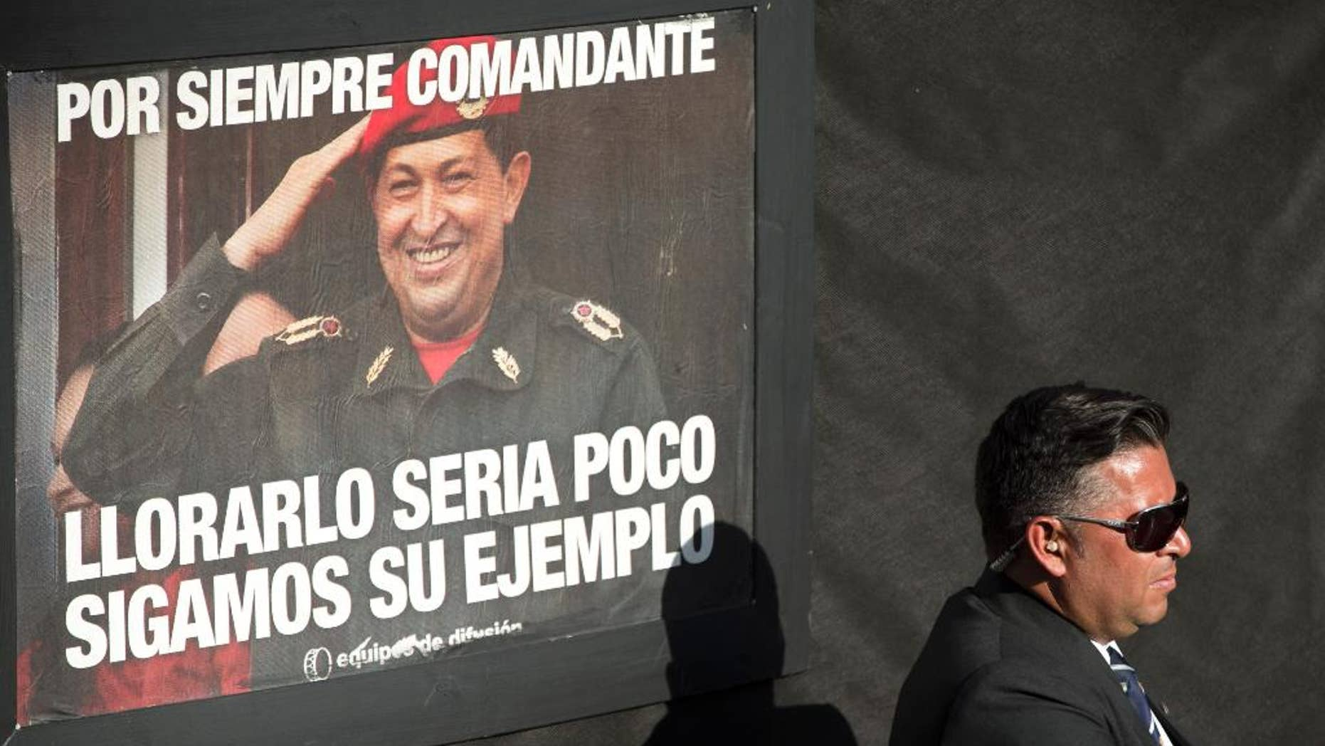"A security officer stands guard near a poster of late Venezuelan President Hugo Chavez that reads in Spanish ""forever commander, crying for him is not enough, let's follow his example"", at mass at the Villa 21 slum in Buenos Aires, Argentina, Wednesday, March 5, 2014. Argentine President Cristina Fernandez attended the mass in honor of Chavez, one year after the Venezuelan leader's death. (AP Photo/Victor R. Caivano)"