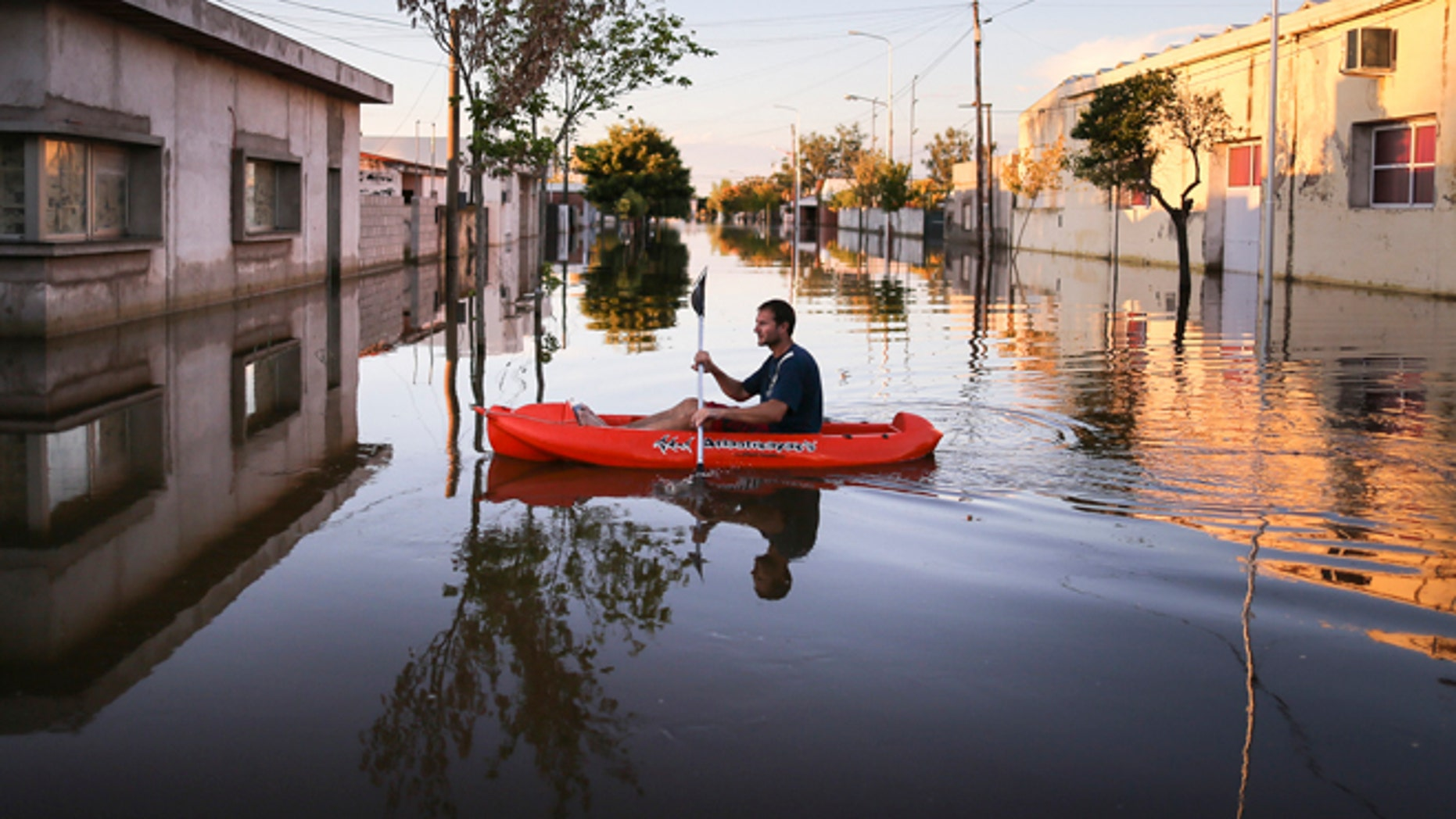 A man rows a dinghy through flood waters in Idiazabal, Argentina, Thursday, March 5, 2015. Flooding throughout four Argentine provinces have forced thousands of people to flee their homes. In the small town of Idiazabal, in the Cordoba province, residents continue to wade through fully submerged streets that have been under water for over one week. While rains stopped on Thursday and are not expected to return over the coming days, floodwaters have not subsided. (AP Photo/Nico Aguilera)