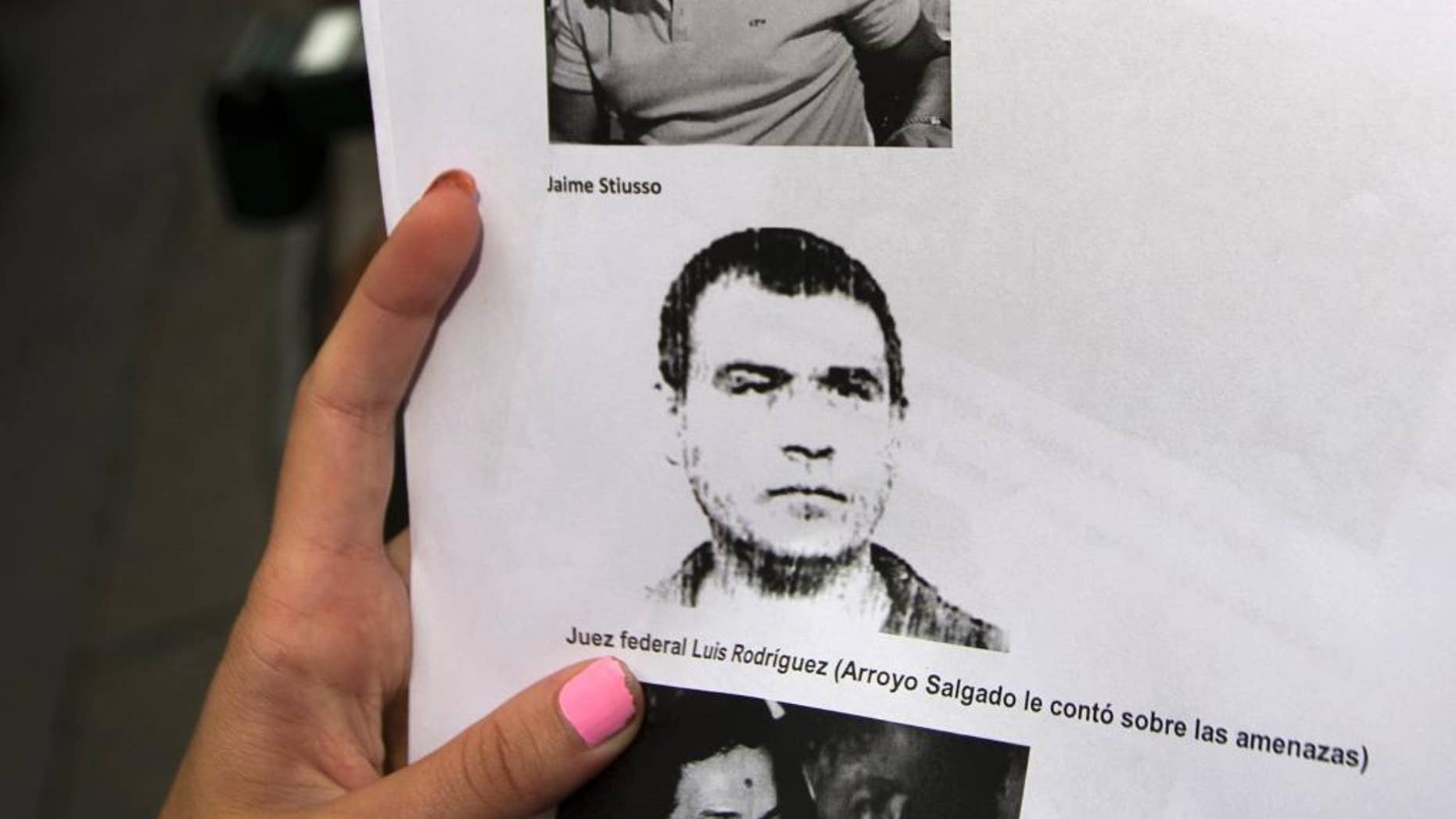 "FILE - In this Feb. 5, 2015 file photo, a reporter holds a copy of a photo of Antonio ""Jaime"" Stiuso, one of the country's most enigmatic spy chiefs, outside the prosecutor's office in Buenos Aires, Argentina. The Argentine government said on Wednesday, Oct. 7, 2015 that the former spymaster it wants to question in the mysterious death of a prosecutor traveled to the U.S. on an Italian passport. President Cristina Fernandez expressed frustration with the U.S. over Stiuso's whereabouts and said American officials had not answered requests to locate him. (AP Photo/Rodrigo Abd, File)"