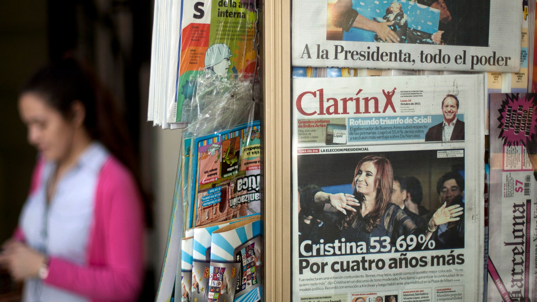 FILE - In this Oct. 24, 2011 file photo, a woman walks by a newspaper stand that displays Argentina's largest circulating daily newspaper the Clarin in Buenos Aires, Argentina. Argentinas government on Saturday, Sept. 22, 2012 gave one of its leading media critics, Grupo Clarin, a Dec. 7 deadline to sell off most of its broadcast stations, saying 7D will stand for diversity and democracy as the day when media monopolies will no longer be able to put themselves above the law.  (AP Photo/Victor R. Caivano, File)