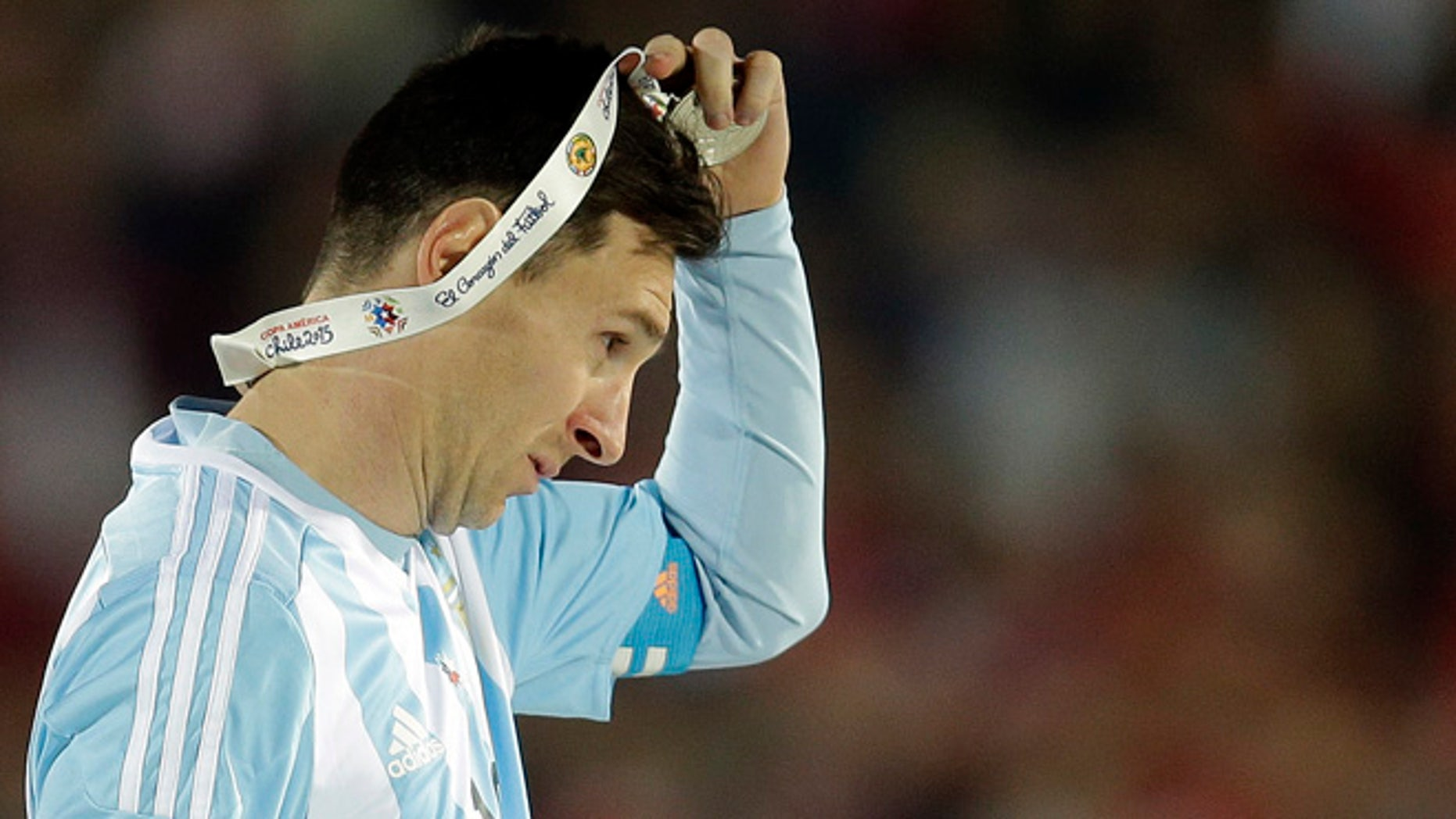 FILE - In this July 4, 2015 file photo, Argentina's Lionel Messi takes off the Copa America silver medal after the final game with Chile at the National Stadium in Santiago, Chile. Messi's shocking decision to stop playing for Argentina could further hurt his already tarnished legacy with his national team. If Messi sticks to his announcement, made in the heat-of-the-moment shortly after Argentina's penalty shootout loss to Chile in Sunday's Copa America final on June 26, 2016, Argentina will be left dwelling on the fact that it was not able to win any significant title while having one of the best players of all time. (AP Photo/Natacha Pisarenko, File)