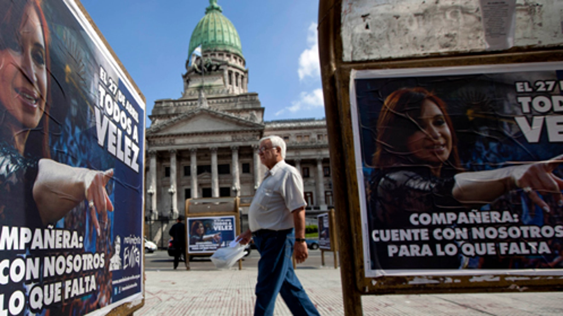"""April 17: A sign of Argentina's President Cristina Fernandez that reads in Spanish """"Companion, count on us for what's left"""" covers a bus stop outside Congress where a bill proposed by Fernandez to gain control of Argentina's energy reserves is being discussed in Buenos Aires. (AP Photo/Natacha Pisarenko)"""