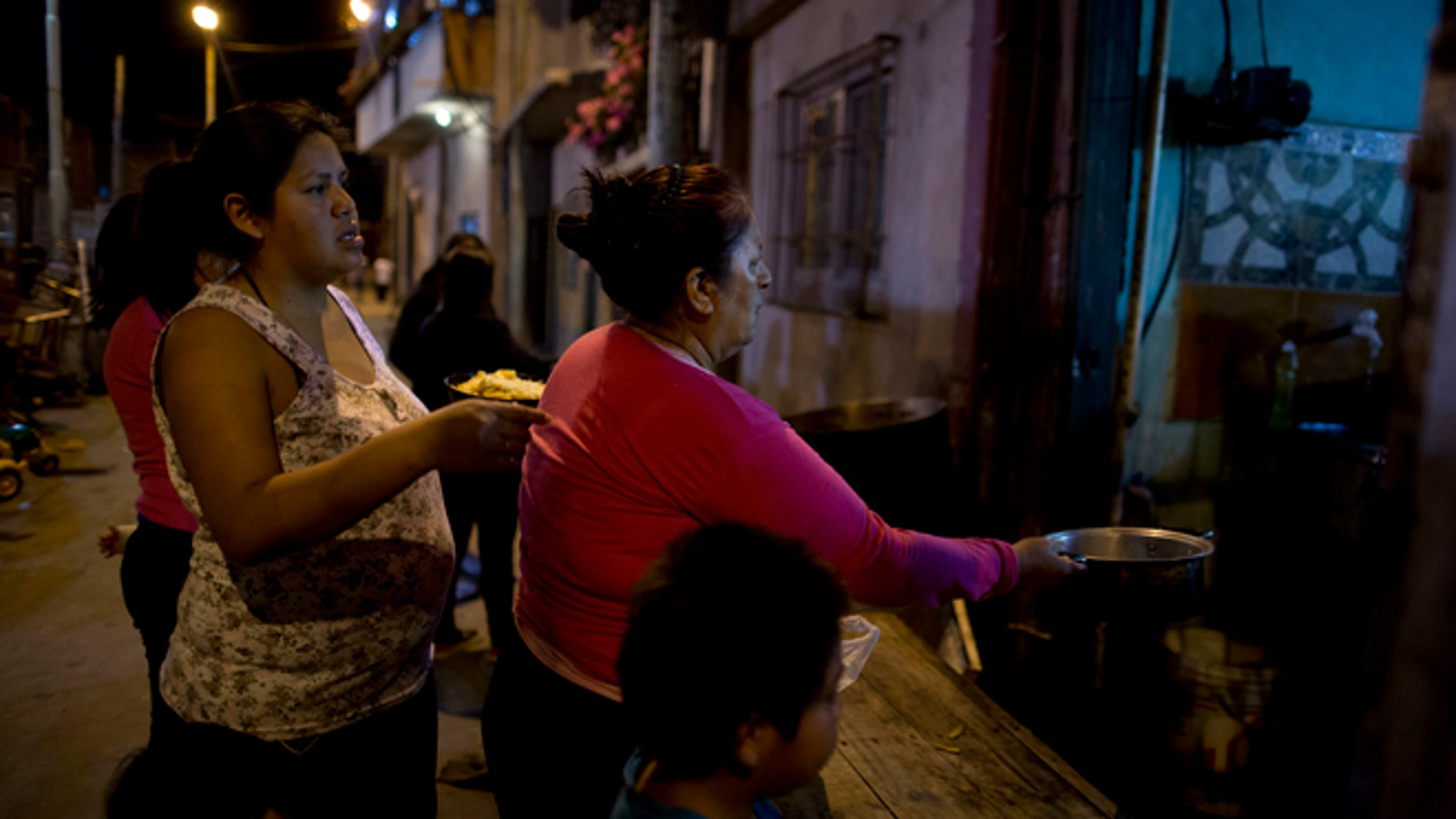 In this Oct. 13, 2016, women line up for a free dinner to take home to their families, from Norma Colque's soup kitchen in the Villa 31 neighborhood of Buenos Aires, Argentina. With the economy expected to shrink by 1.5 percent this year, President Mauricio Macri now admits his poverty goal isn't possible, and discontent is growing. (AP Photo/Natacha Pisarenko)