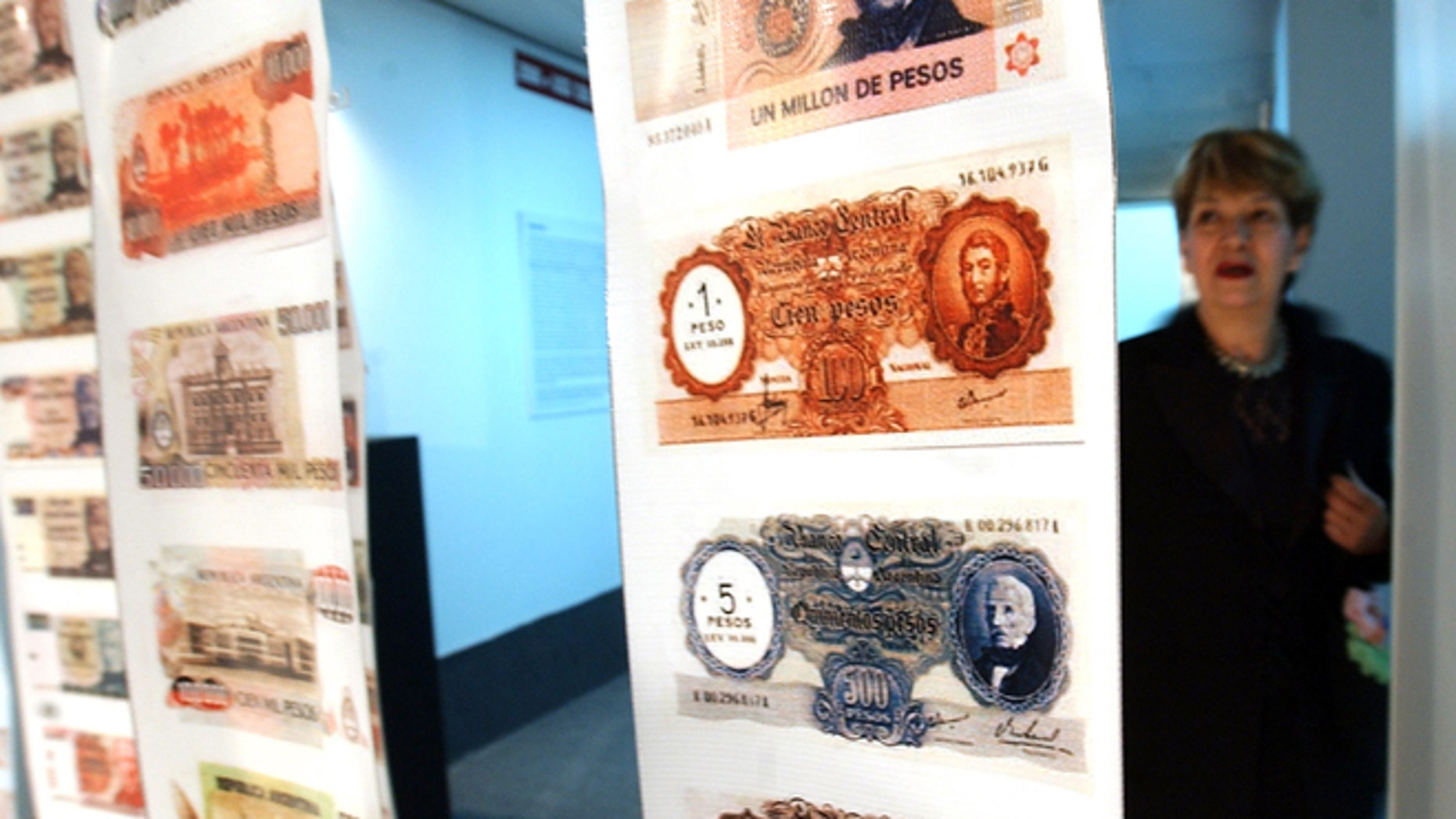 FILE - In this April, 28, 2005, file photo, a woman looks at old currency during the opening of the Foreign Debt Museum in Buenos Aires, Argentina.  The museum, which is the world's first dedicated to a country's debt, opened nearly four years after Argentina staged the largest debt default in modern history. Argentine President Cristina Fernandez said Monday June 16, 2014 that Argentina can't comply with U.S. court orders to pay $1.5 billion to winners of a decade-long legal battle over defaulted debt, the position her country was left in Monday when the U.S. Supreme Court refused to hear her government's final appeal. (AP Photo/Natacha Pisarenko,File)