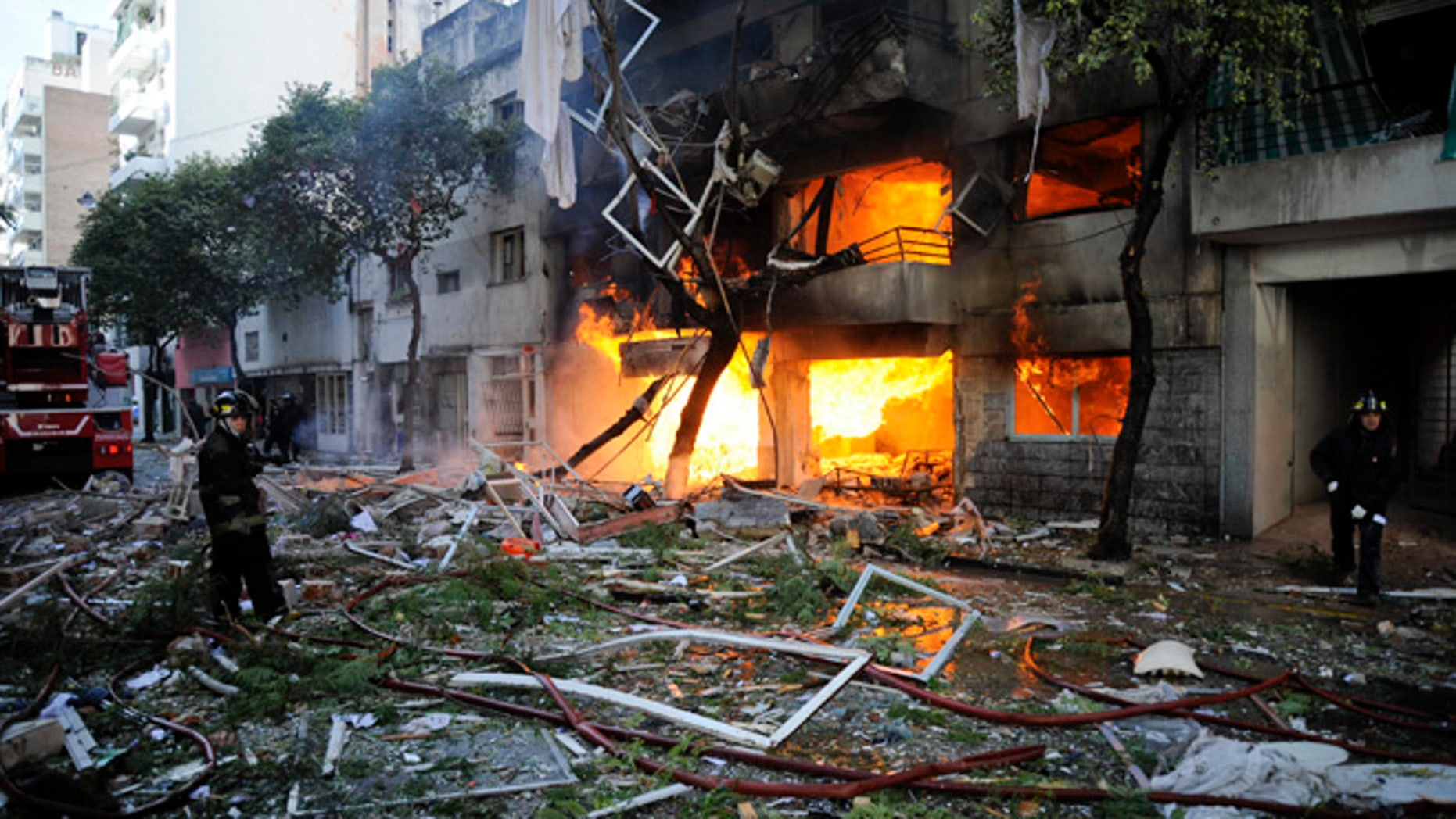 Aug. 6, 2013: Firemen stand in debris caused by a gas explosion that has severely damaged a multi-story apartment building in Rosario, Argentina.