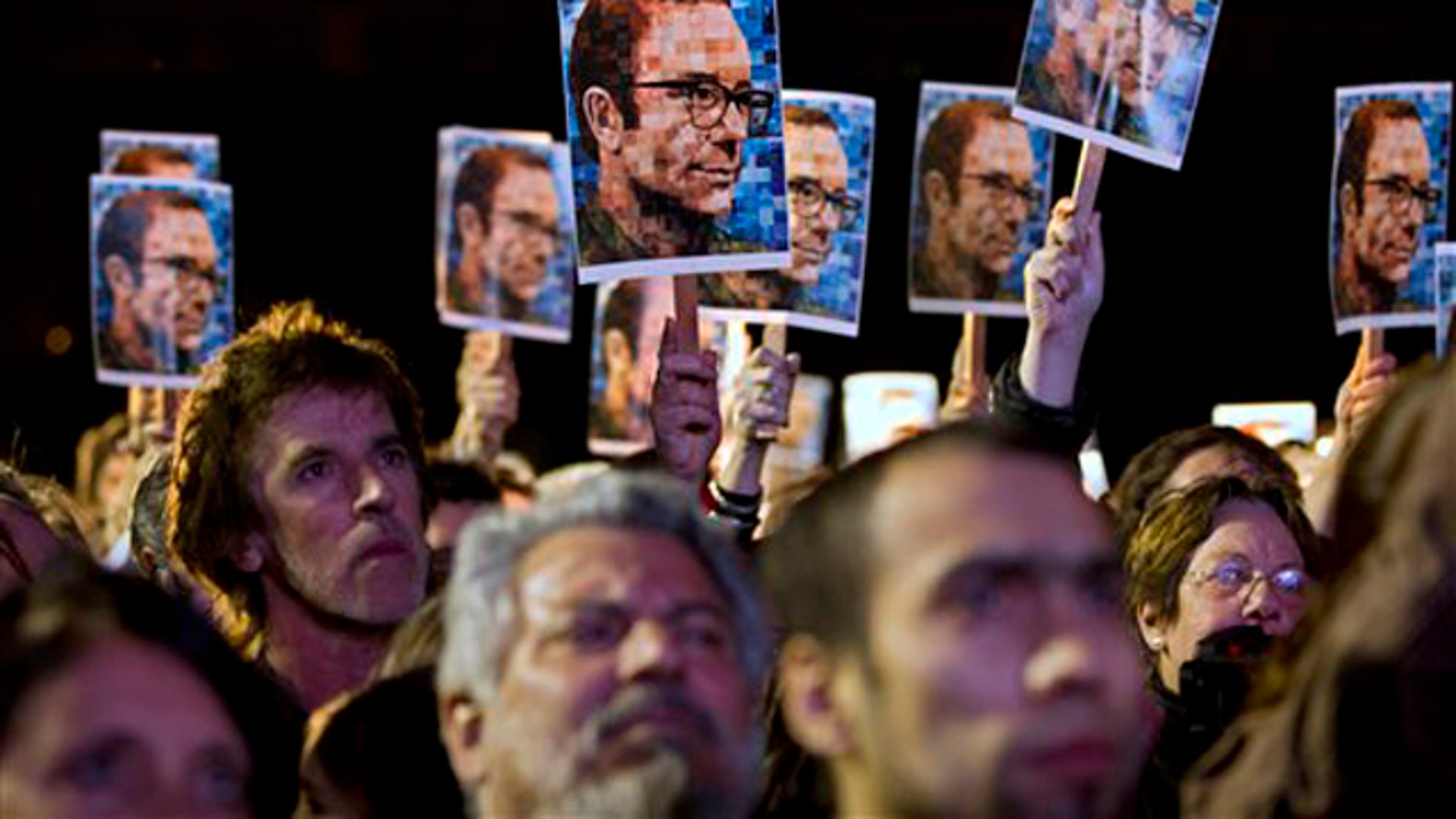 Oct. 26, 2011: People hold up photos of Argentine missing journalist and writer Rodolfo Walsh as they wait for the verdict of a trial against former military and police officials in Buenos Aires, Argentina on Wednesday.