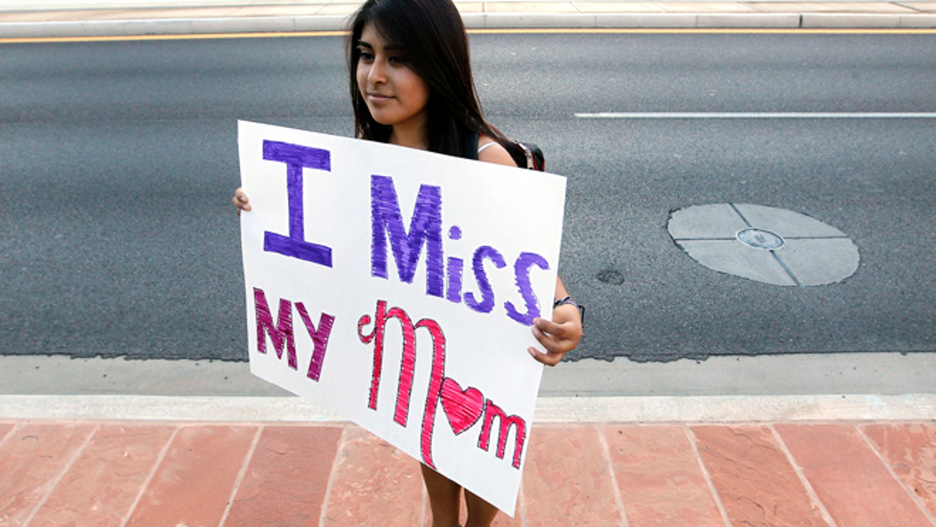 At a protest on Sept. 19, Cynthia Diaz holds up a sign as she joins dozens who rally in front of  U.S. Immigration and Customs Enforcement building, a day after a portion of Arizona's immigration law took effect in Phoenix.
