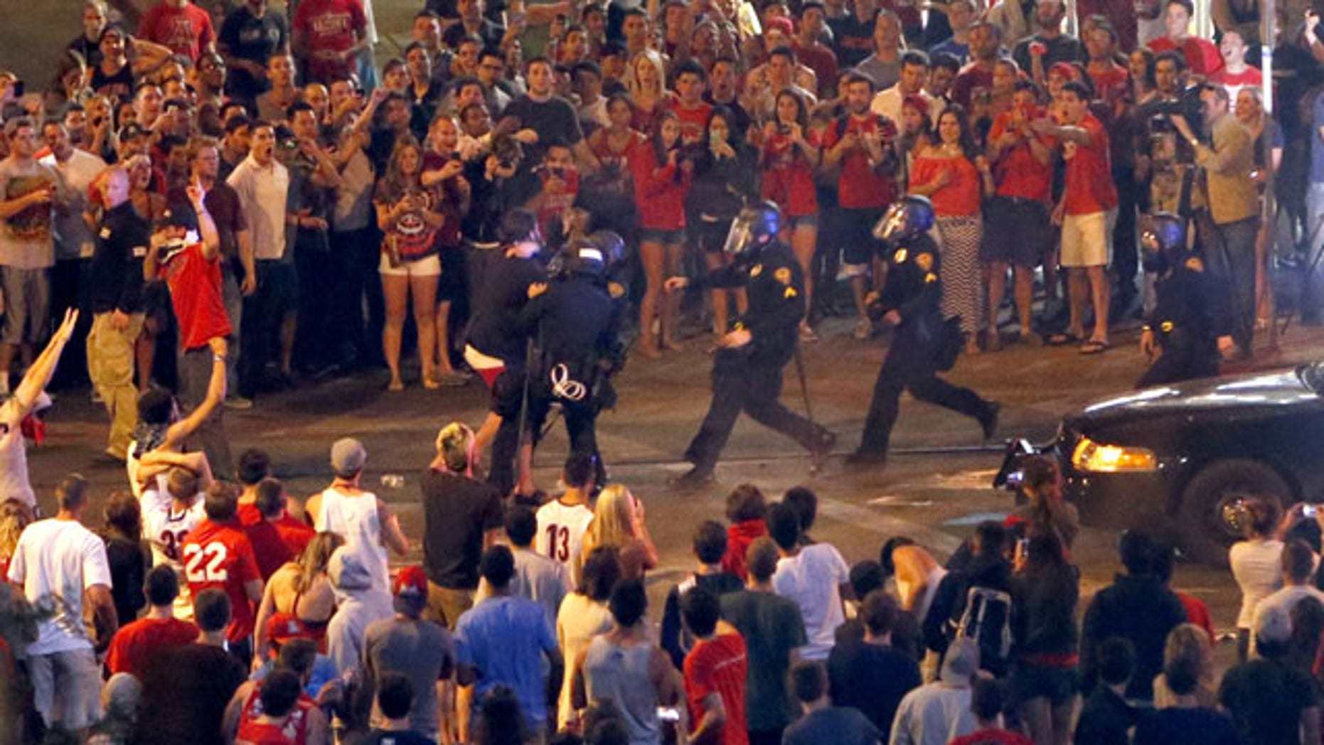 March 29, 2014: Tucson Police Officers rush out of their line to take a man into custody who had been taunting them and riling up a crowd of fans in Maingate Square in Tucson, Ariz. following Arizona's loss to Wisconsin 64-63 in the West Region NCAA final. (AP Photo/Arizona Daily Star, Kelly Presnell)