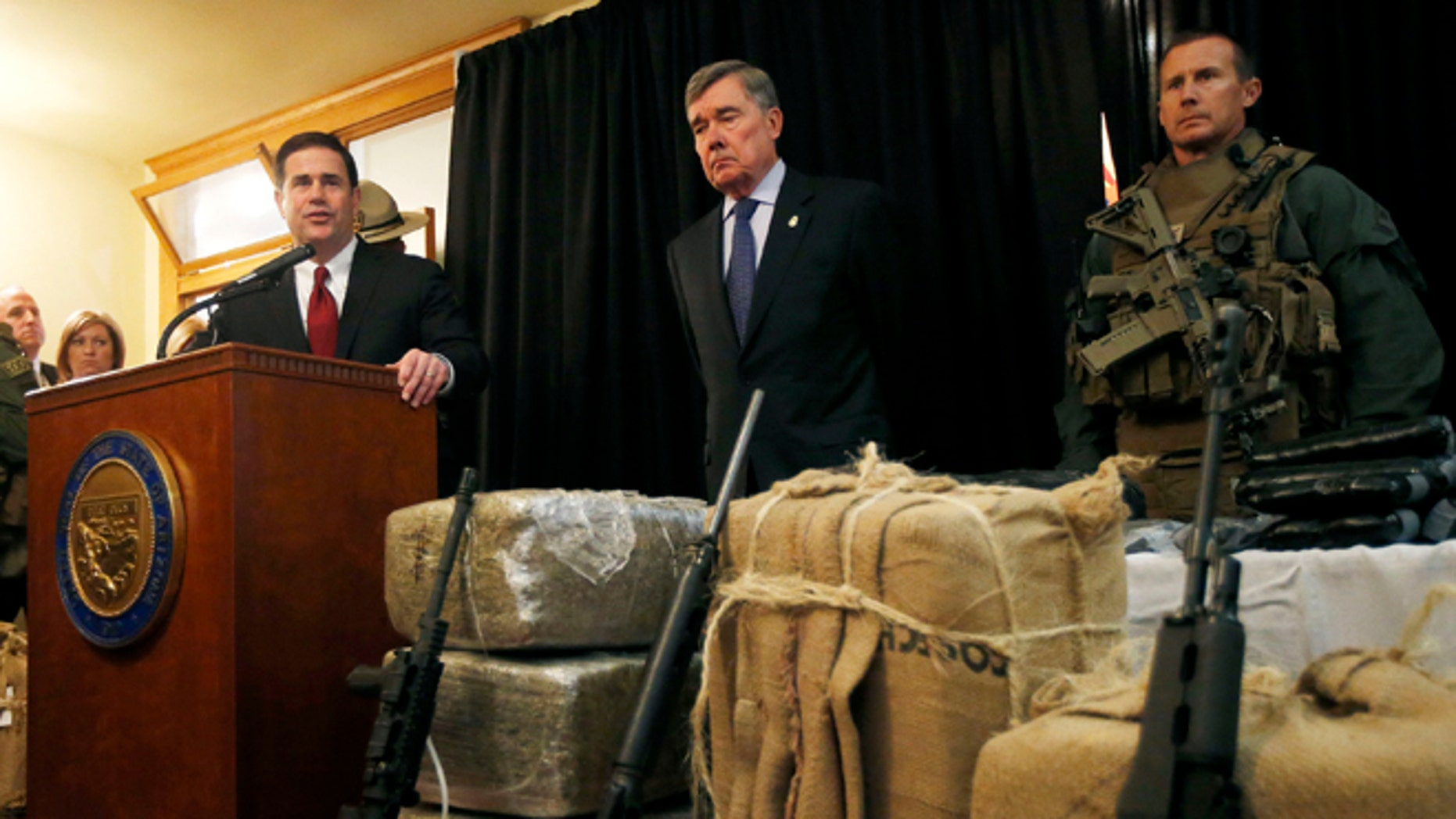 With seized drugs and weapons from border-crossing drug smugglers, Arizona Gov. Doug Ducey, left, speaks at a news conference after testifying at a field hearing of the U.S. Senate Homeland Security and Governmental Affairs Committee at the Arizona Capitol Monday, Nov. 23, 2015, in Phoenix.  R. Gil Kerlikowske, center, commissioner of the U.S. Customs and Border Protection, listens in during the news conference. (AP Photo/Ross D. Franklin)