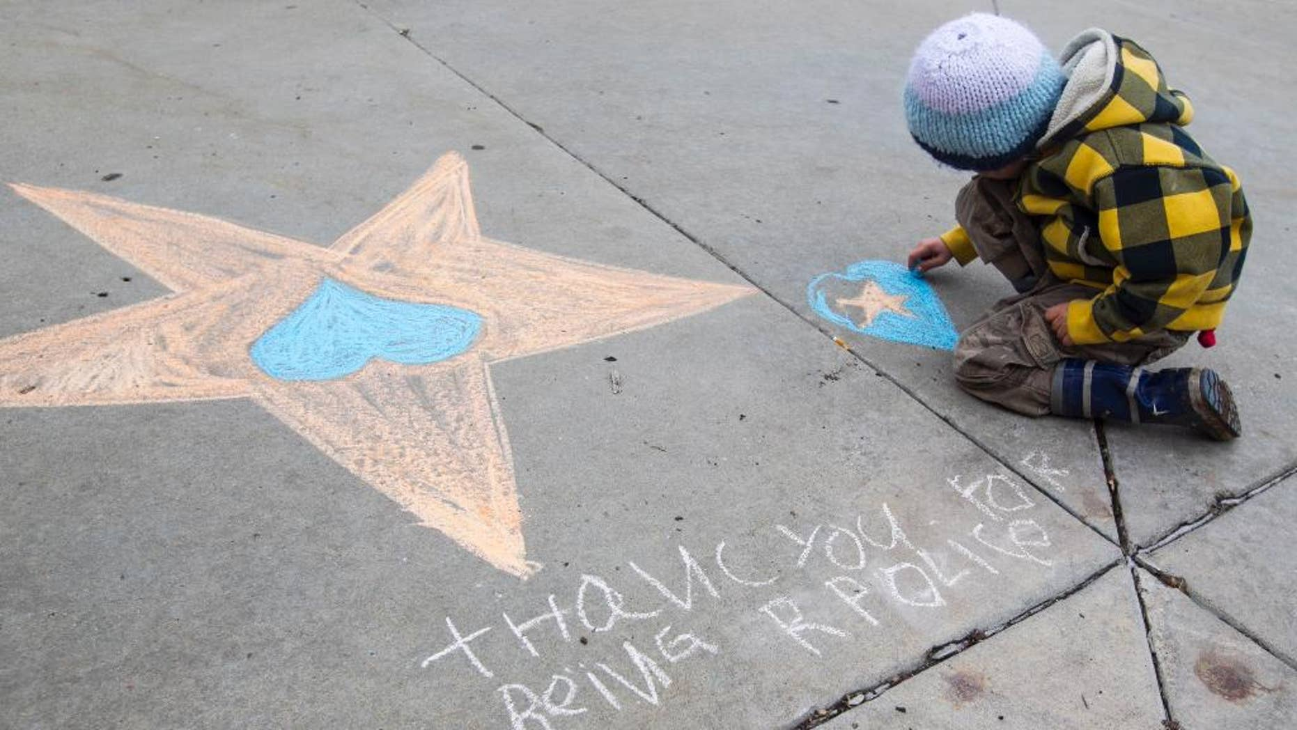 """Caspian Carpenter, 5, draws a star with a heart and words that say """"Thank you for being R police"""" Sunday, Dec. 28, 2014, at the Flagstaff Police Department a day after officer Tyler Stewart was shot and killed in Flagstaff, Ariz.  (AP Photo/The Arizona Republic, Patrick Breen)"""