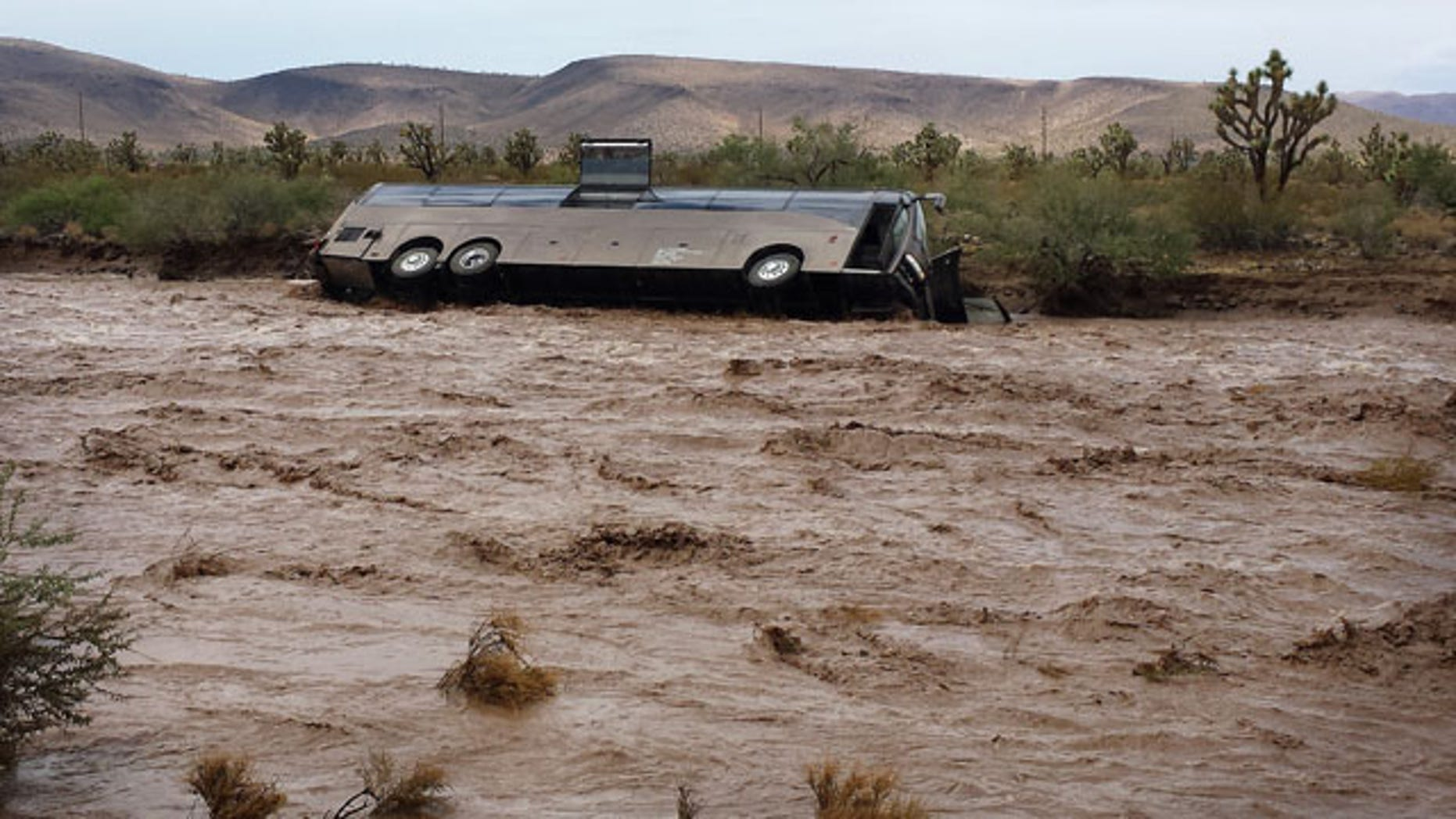 July 28, 2013: This photo released by the Northern Arizona Consolidated Fire District shows a Las Vegas-bound tour bus lies on its side in a flooded desert wash near Dolan Springs, Ariz. after being swept away by floodwaters amid heavy rains. (AP Photo)